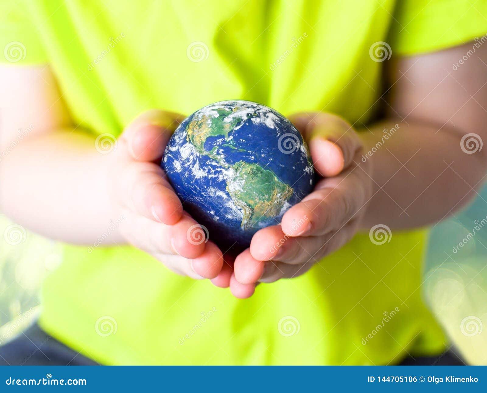 Crian?a pequena em um t-shirt verde que guarda a terra do planeta em suas m?os Dia de terra Conceito verde
