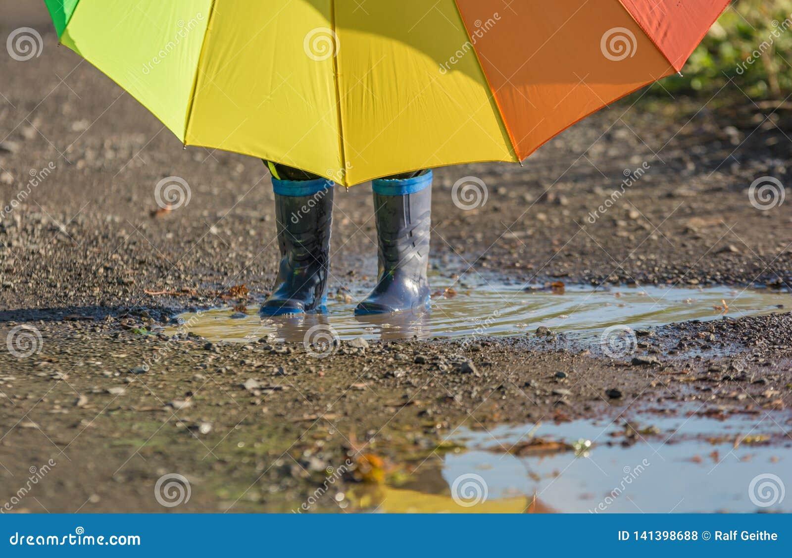 A criança pequena está com botas de borracha em uma poça que guarda um guarda-chuva grande