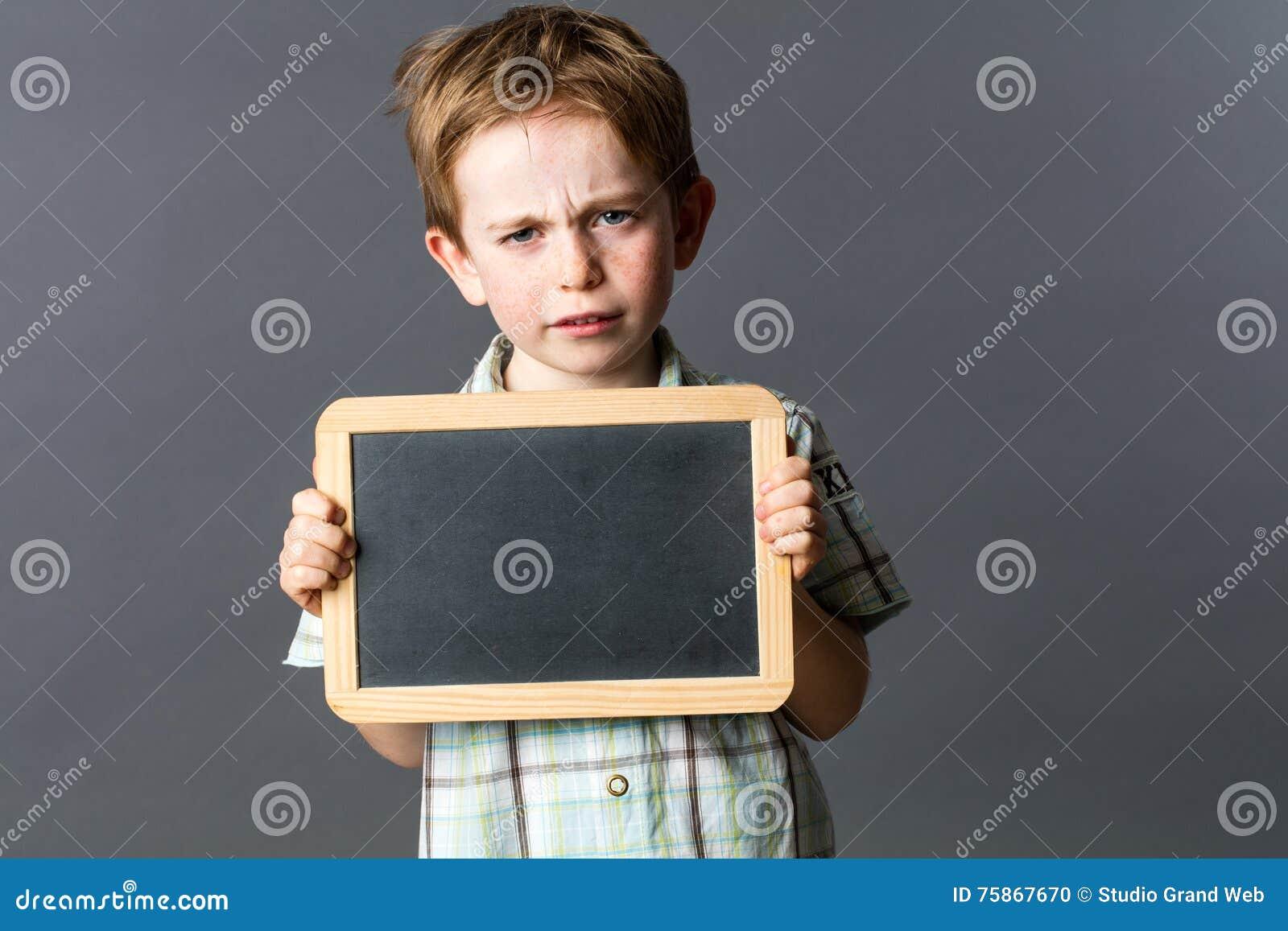 Criança pequena infeliz que mostra a ardósia vazia da escrita à reflexão expressa