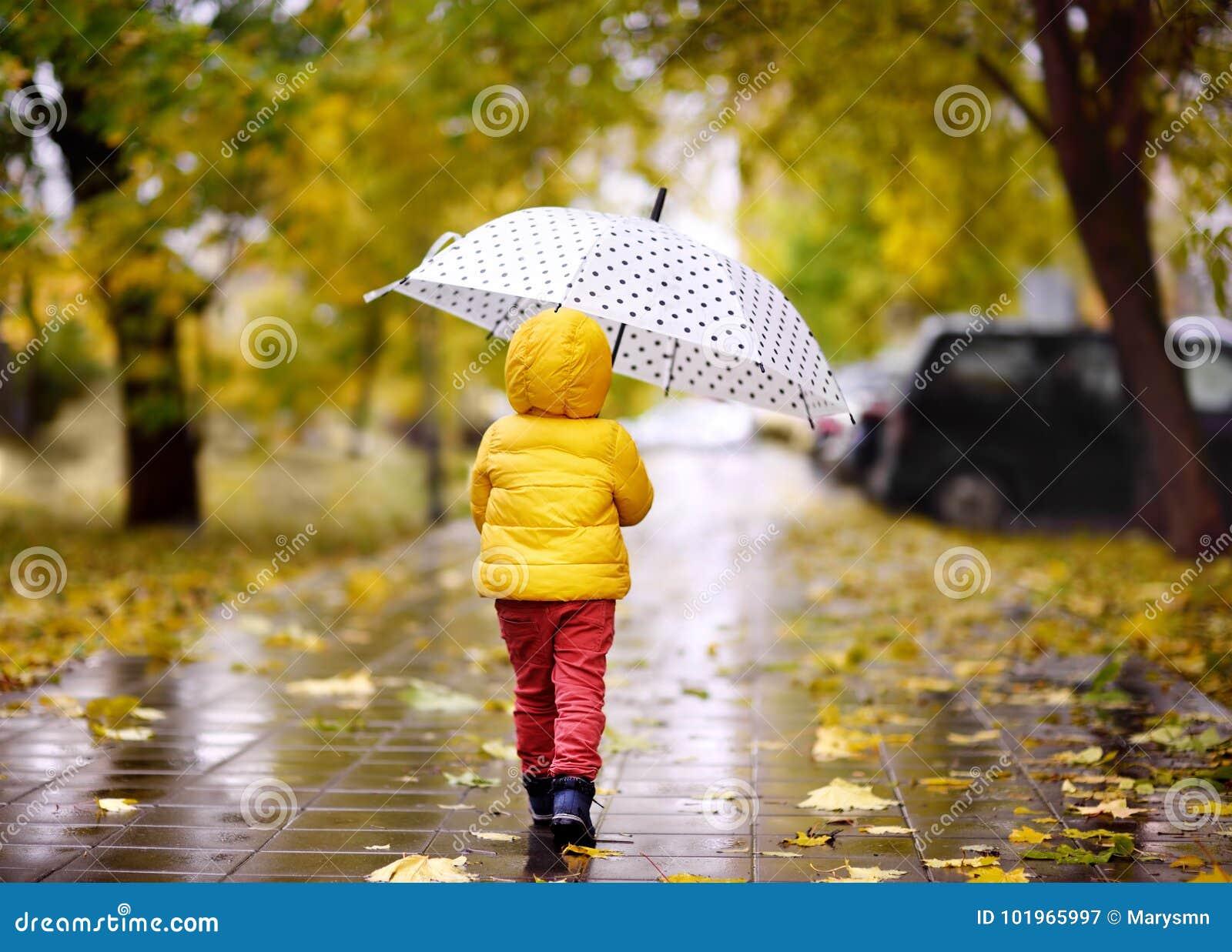 Criança pequena que anda no parque da cidade no dia chuvoso do outono