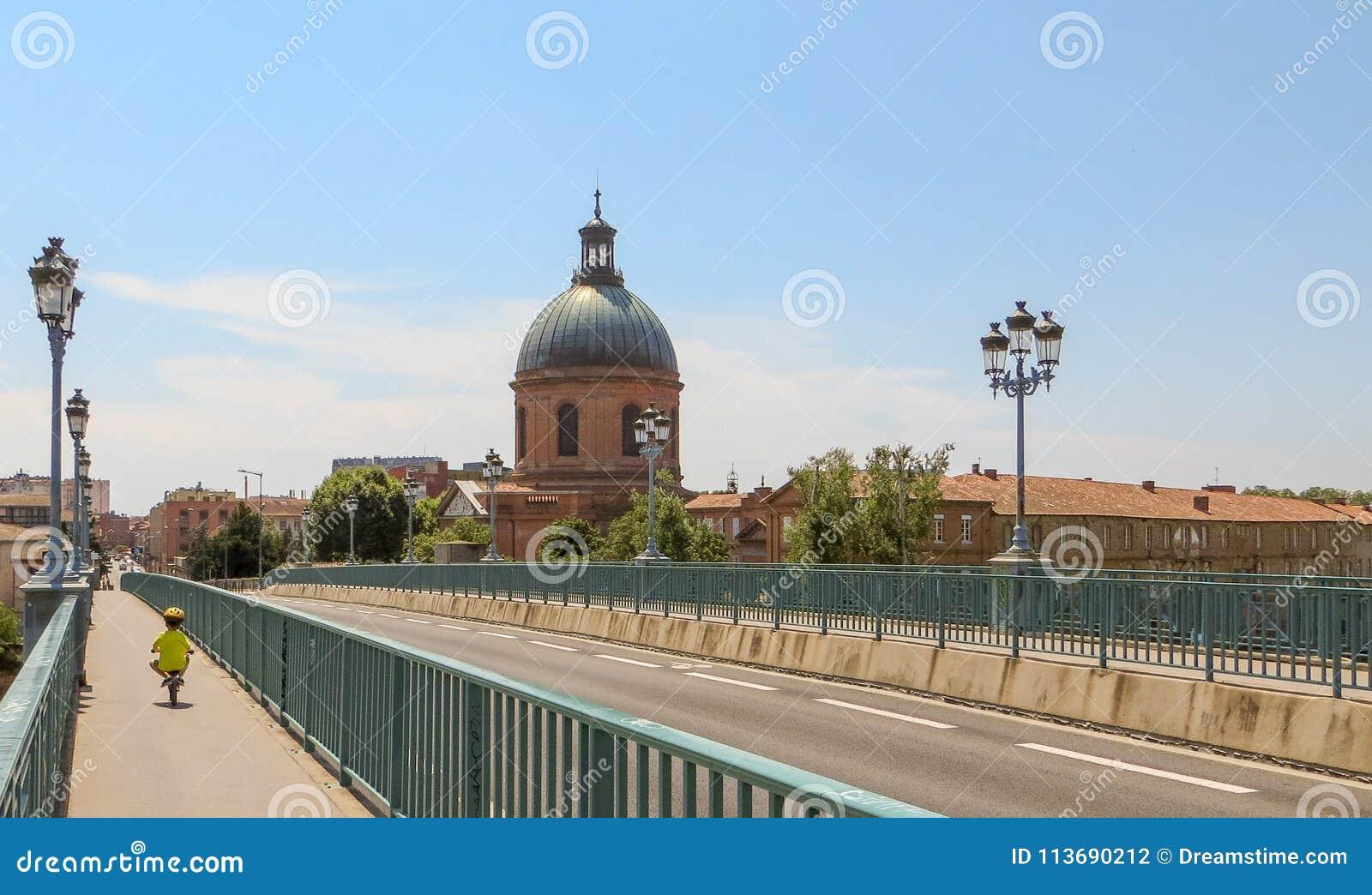 Criança pequena que monta uma bicicleta com segurança na pista da bicicleta em uma ponte europeia cênico