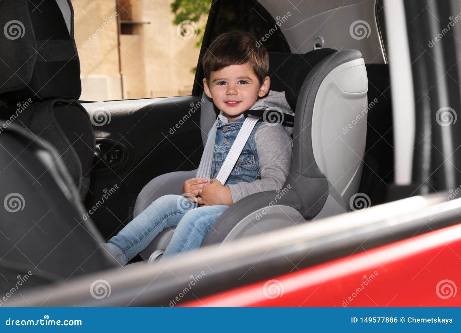 Criança pequena que senta-se no assento da segurança dentro do carro Prevenção do perigo