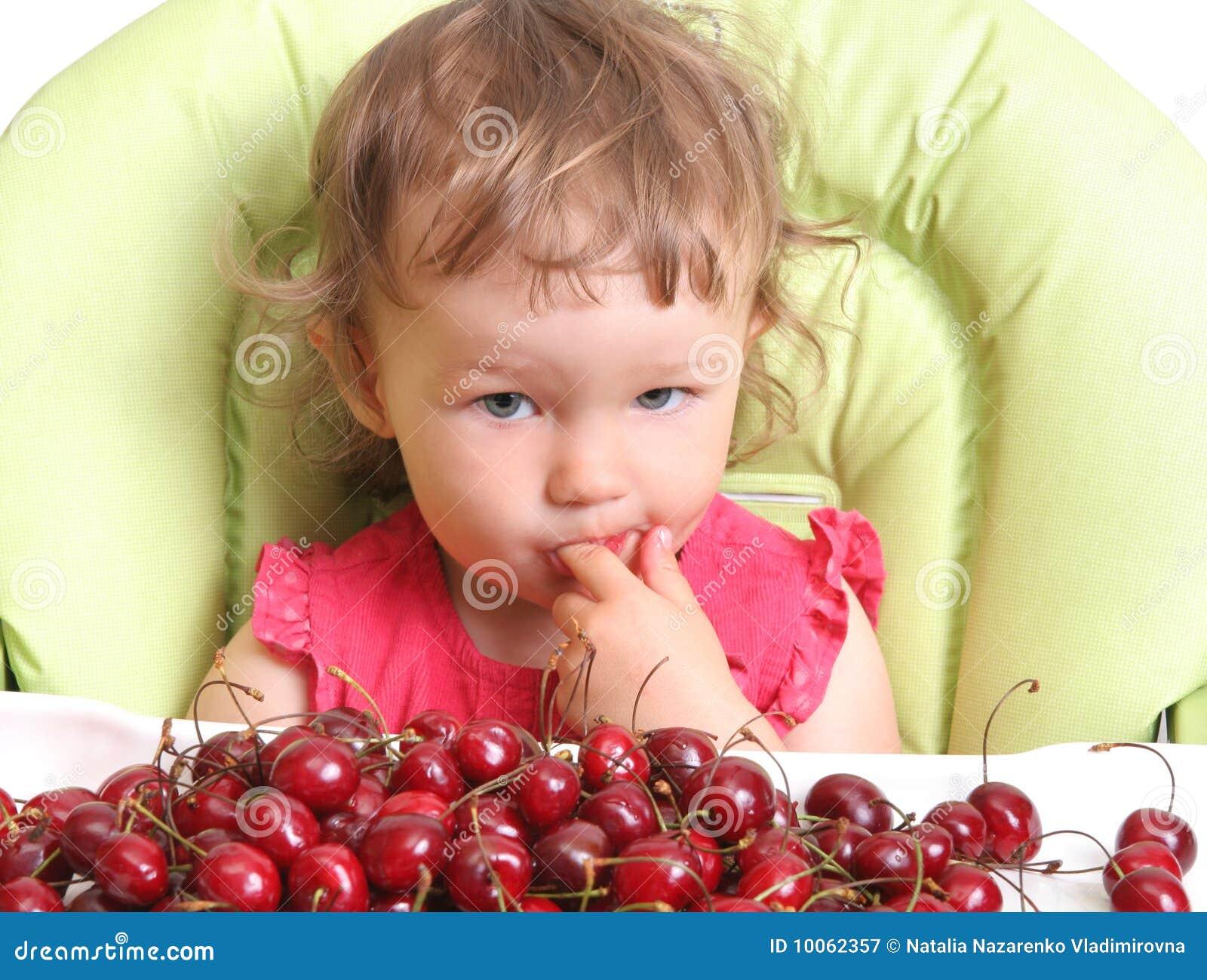 A criança prova a cereja