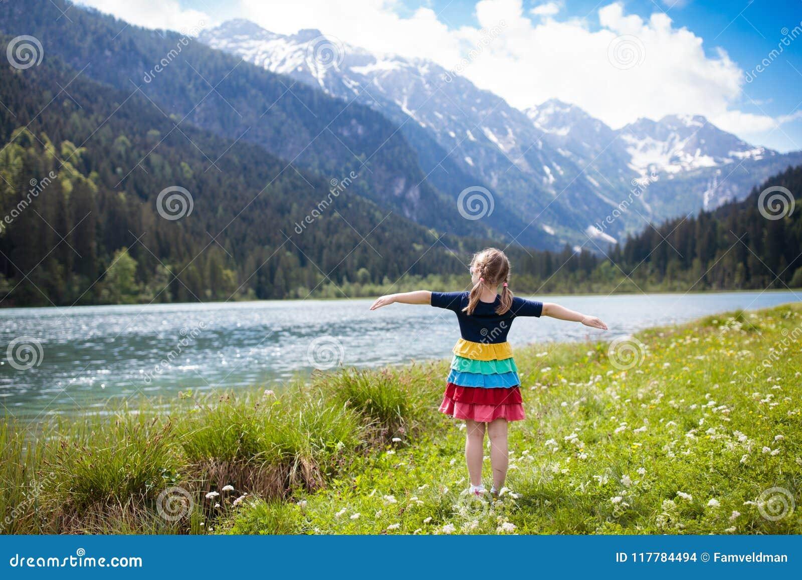 Criança que caminha no campo de flor no lago da montanha