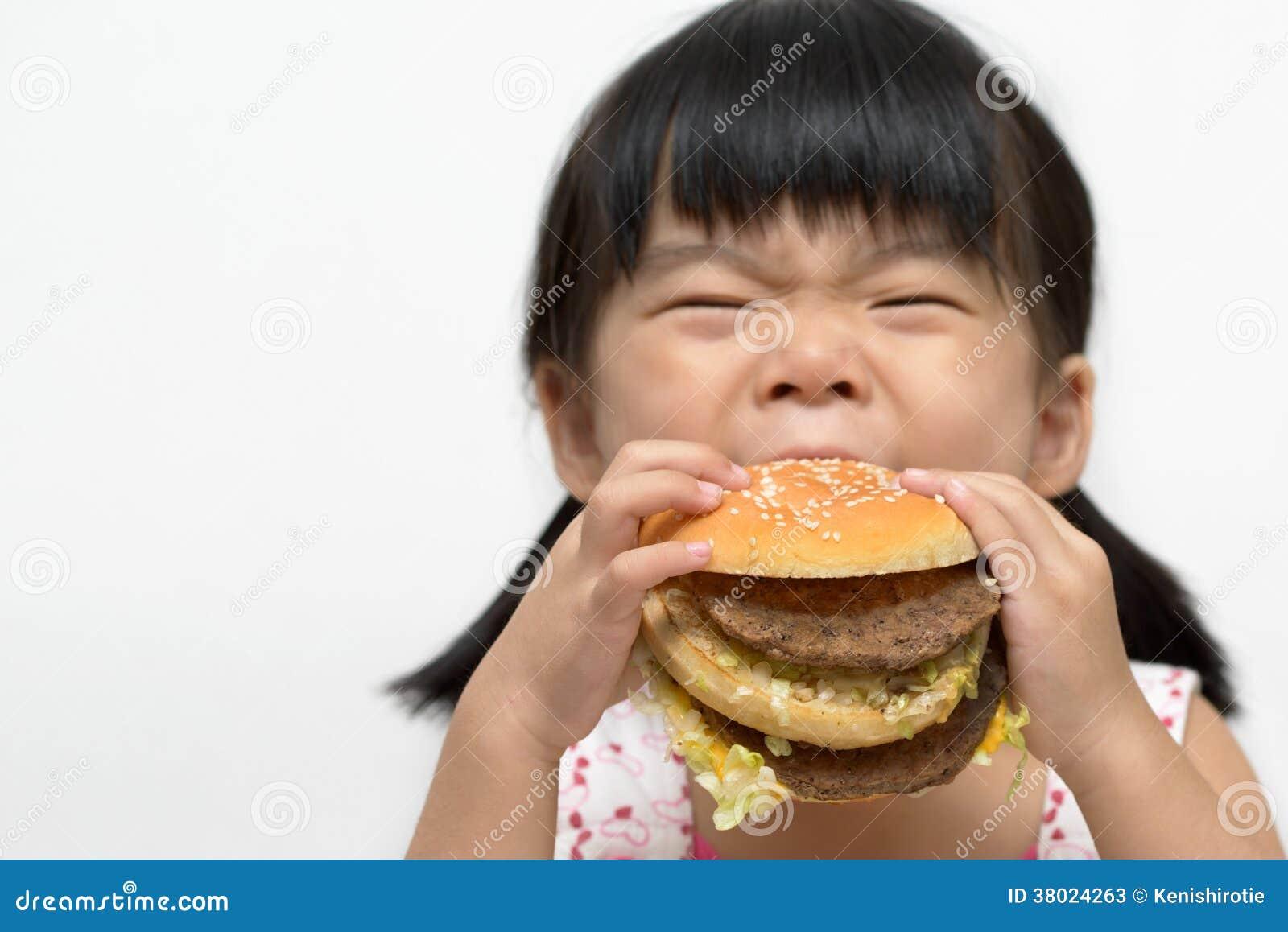Criança que come o hamburguer grande