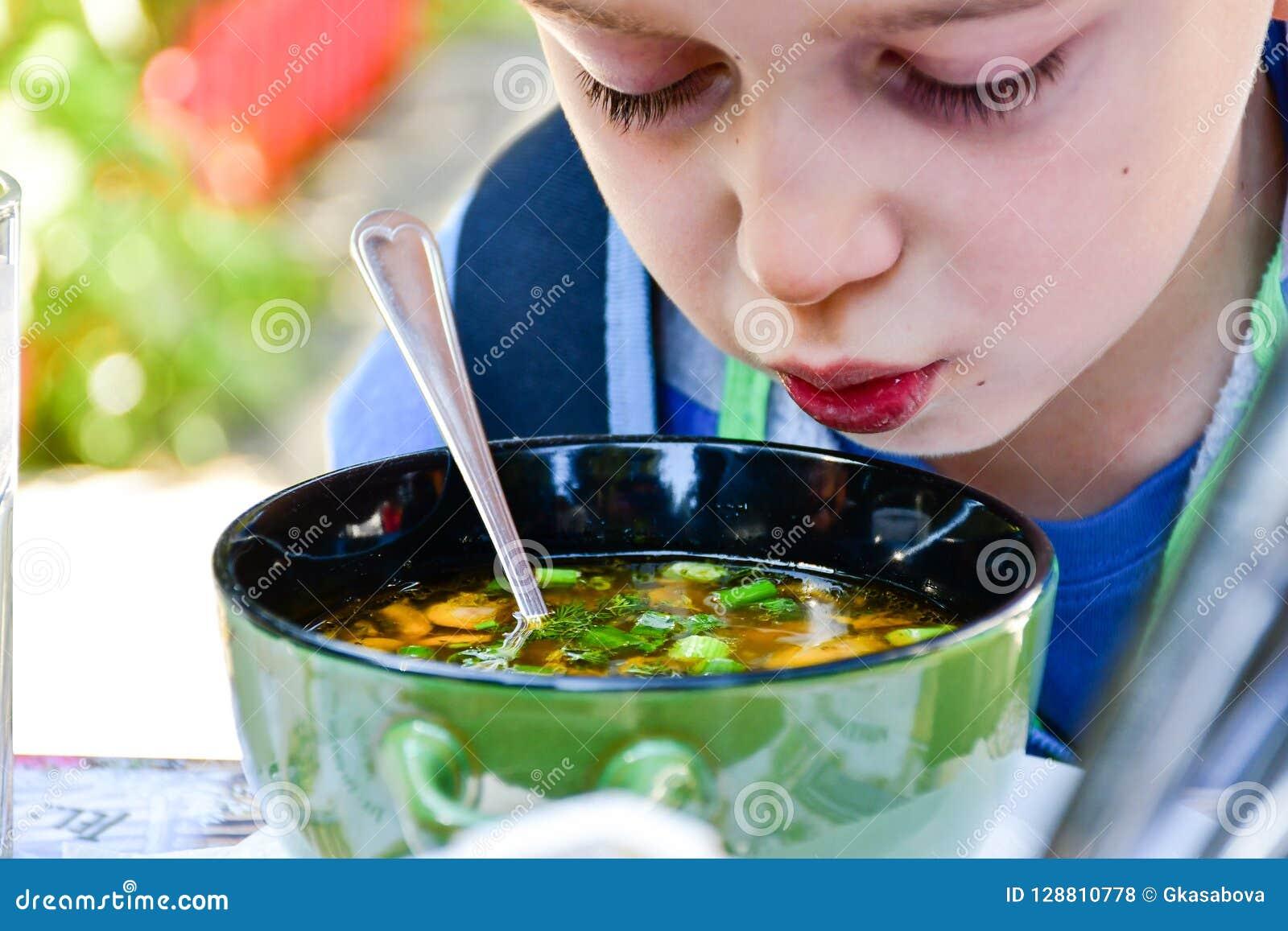 Criança que come uma sopa
