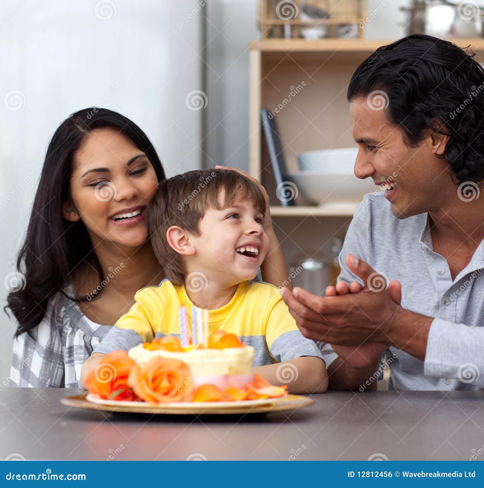 Criança que comemora seu aniversário com seus pais