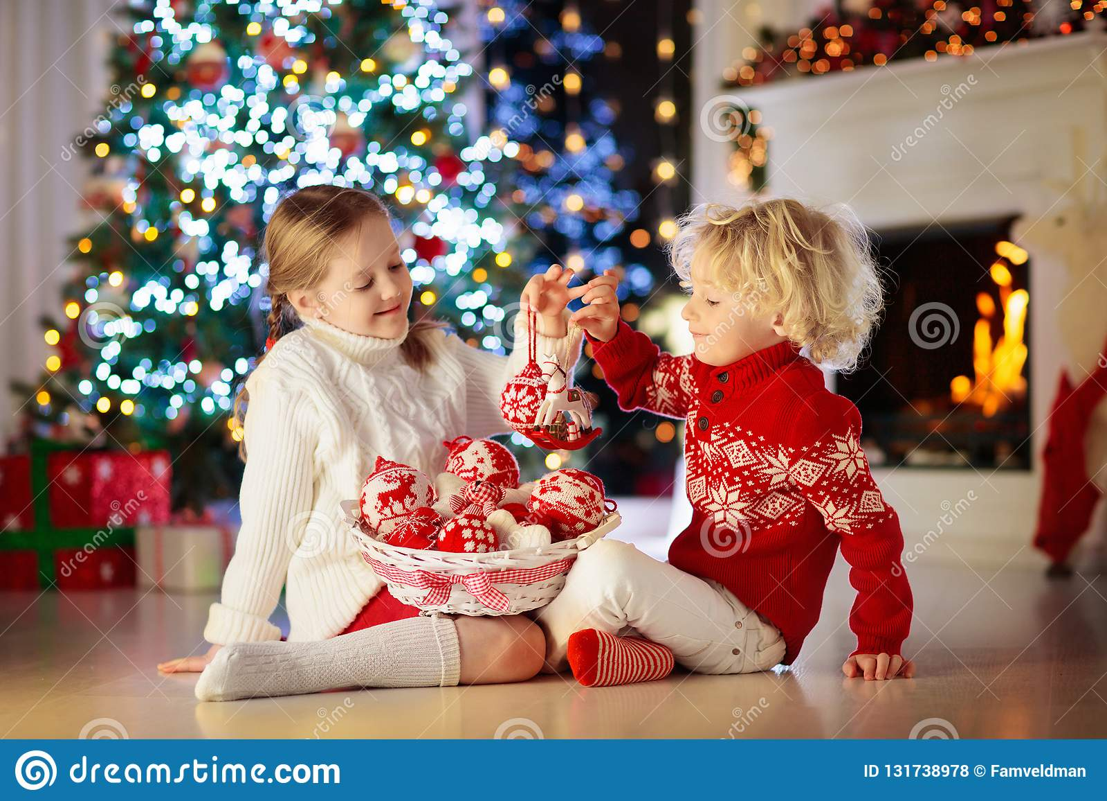 Criança que decora a árvore de Natal em casa Rapaz pequeno e menina na camiseta feita malha com o ornamento feito a mão do Xmas C