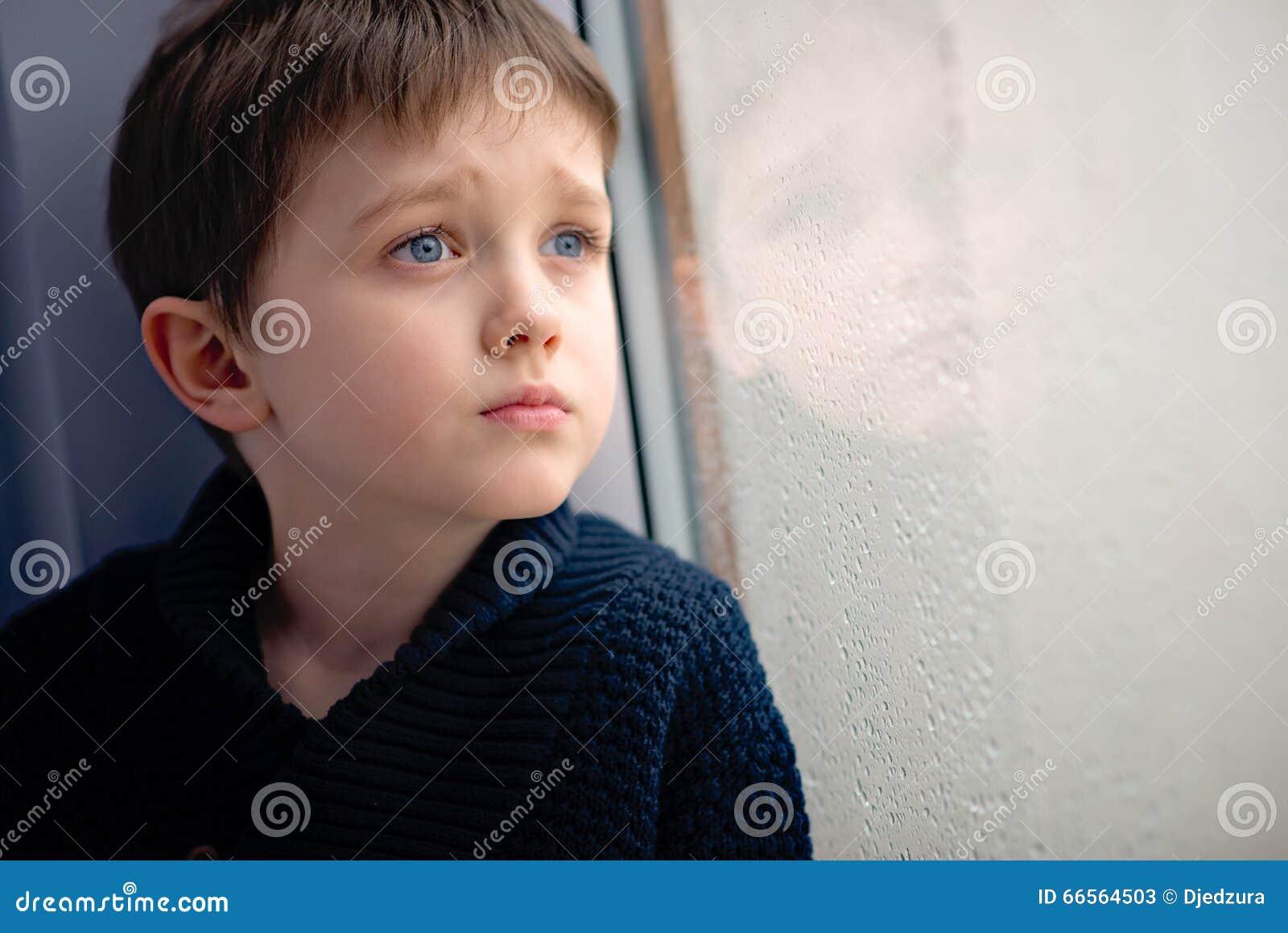 Criança que espera pela janela chover da parada