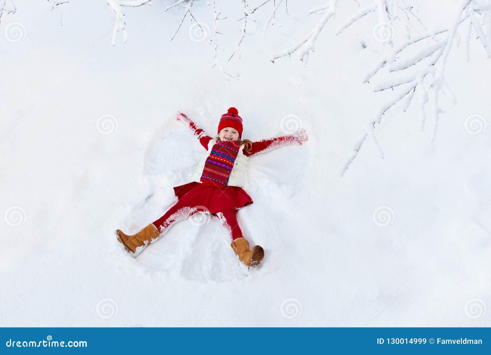 Criança que faz o anjo da neve Divertimento exterior do inverno das crianças