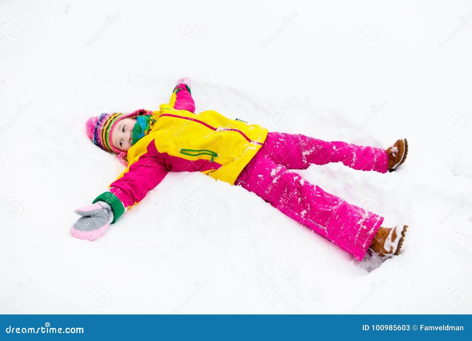 Criança que faz o anjo da neve Jogo das crianças no parque do inverno