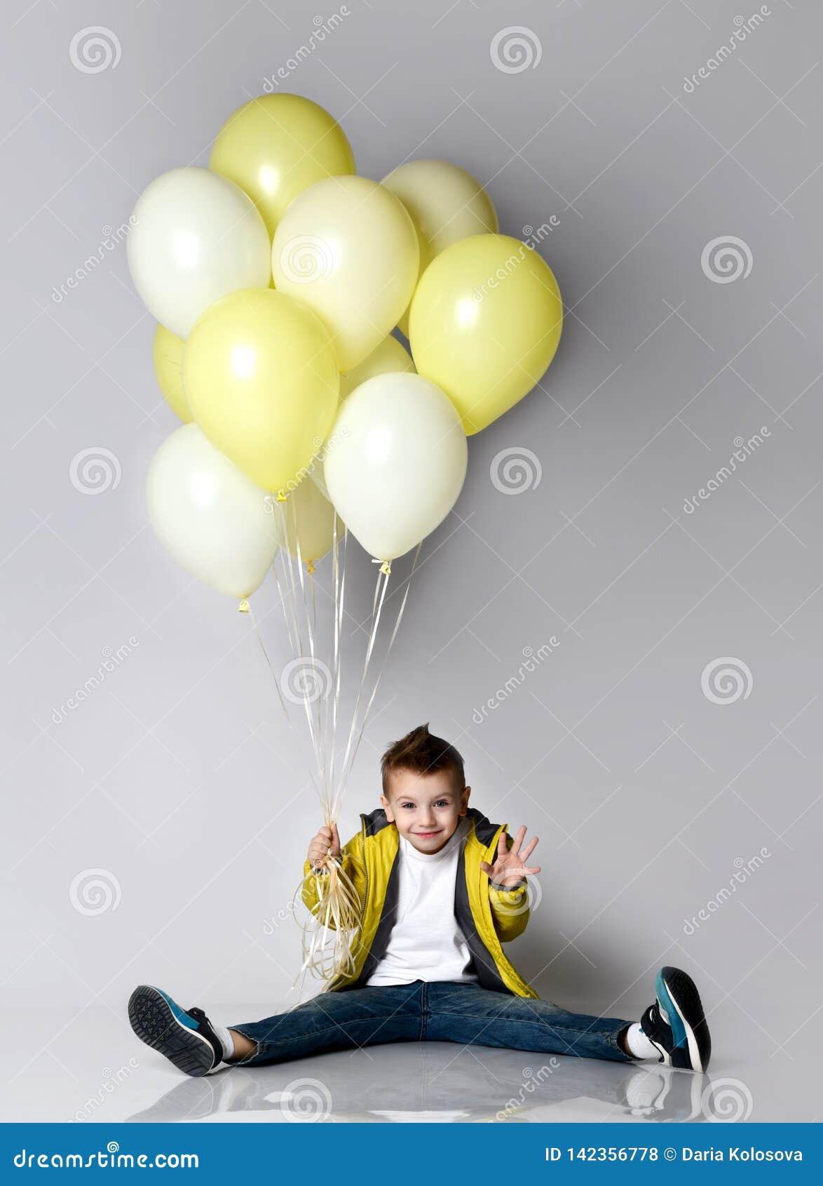 Criança que guarda o grupo dos balões que ficam no joelho sobre o fundo branco