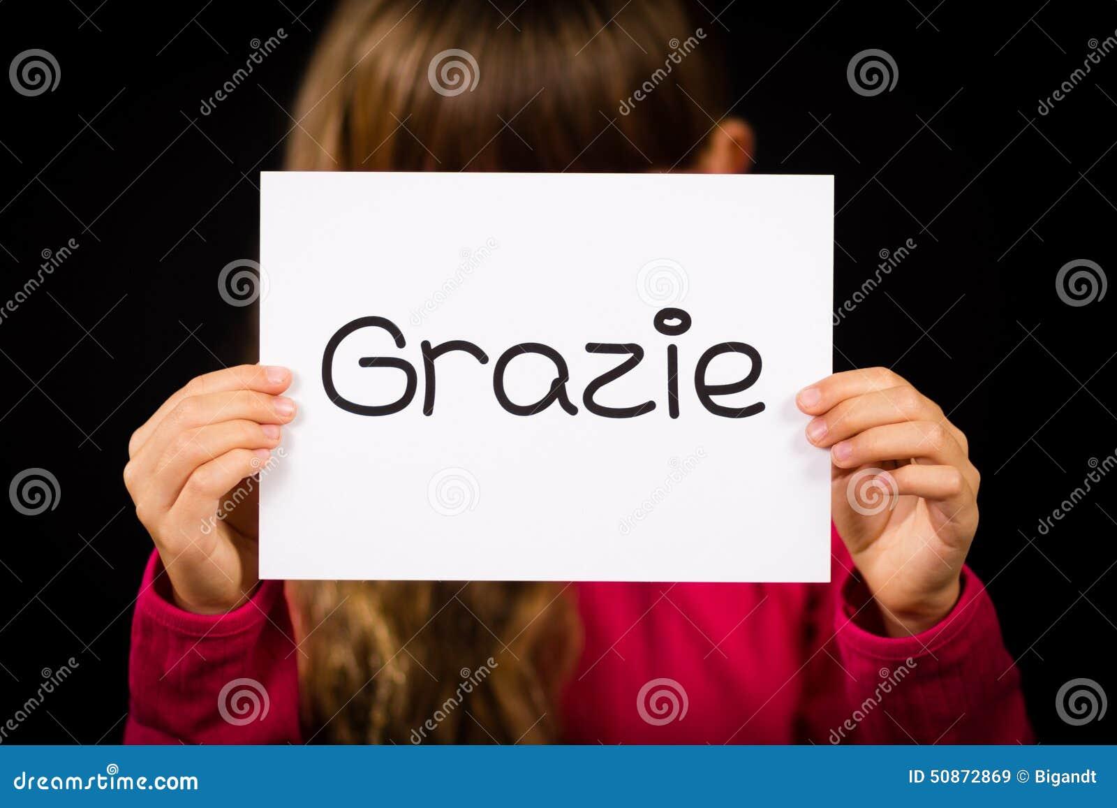 Criança que guarda o sinal com palavra italiana Grazie - obrigado