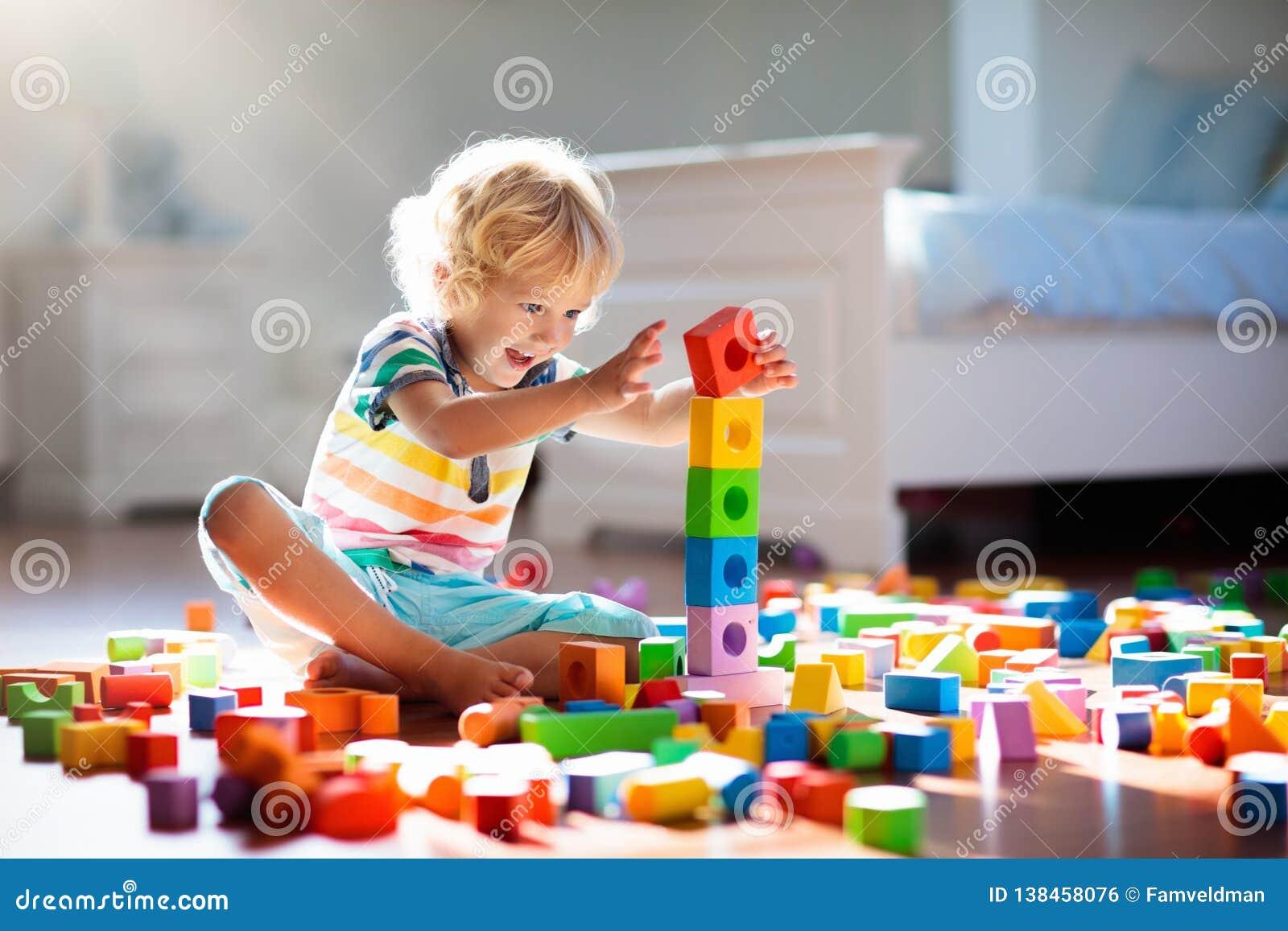 Criança que joga com blocos coloridos do brinquedo Jogo das crianças