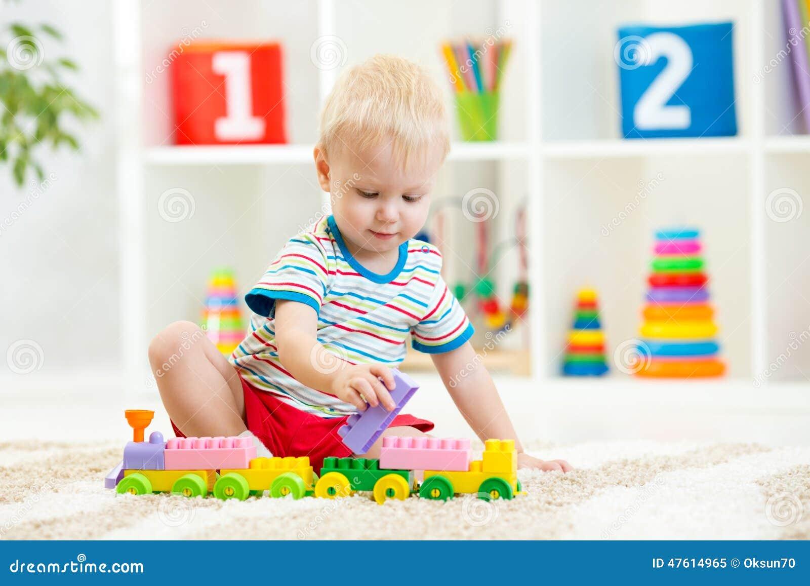 Criança que joga com blocos de apartamentos no jardim de infância