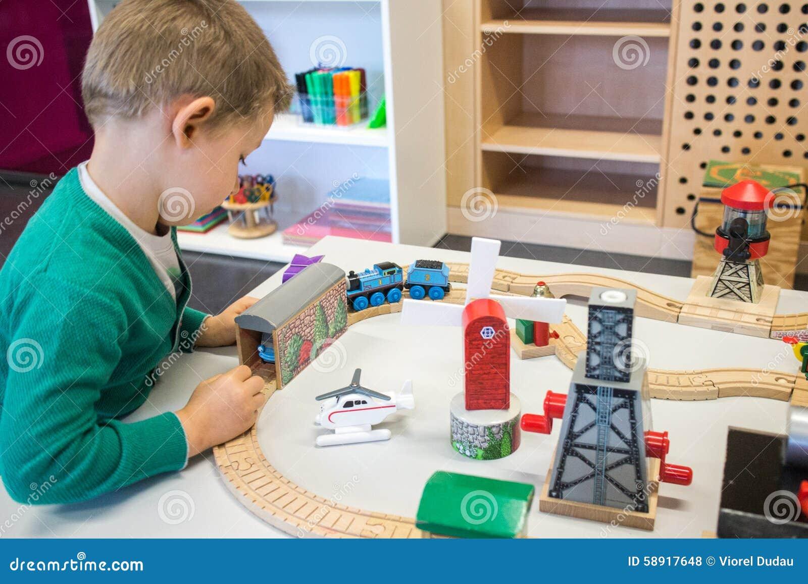 Criança que joga com trem do brinquedo