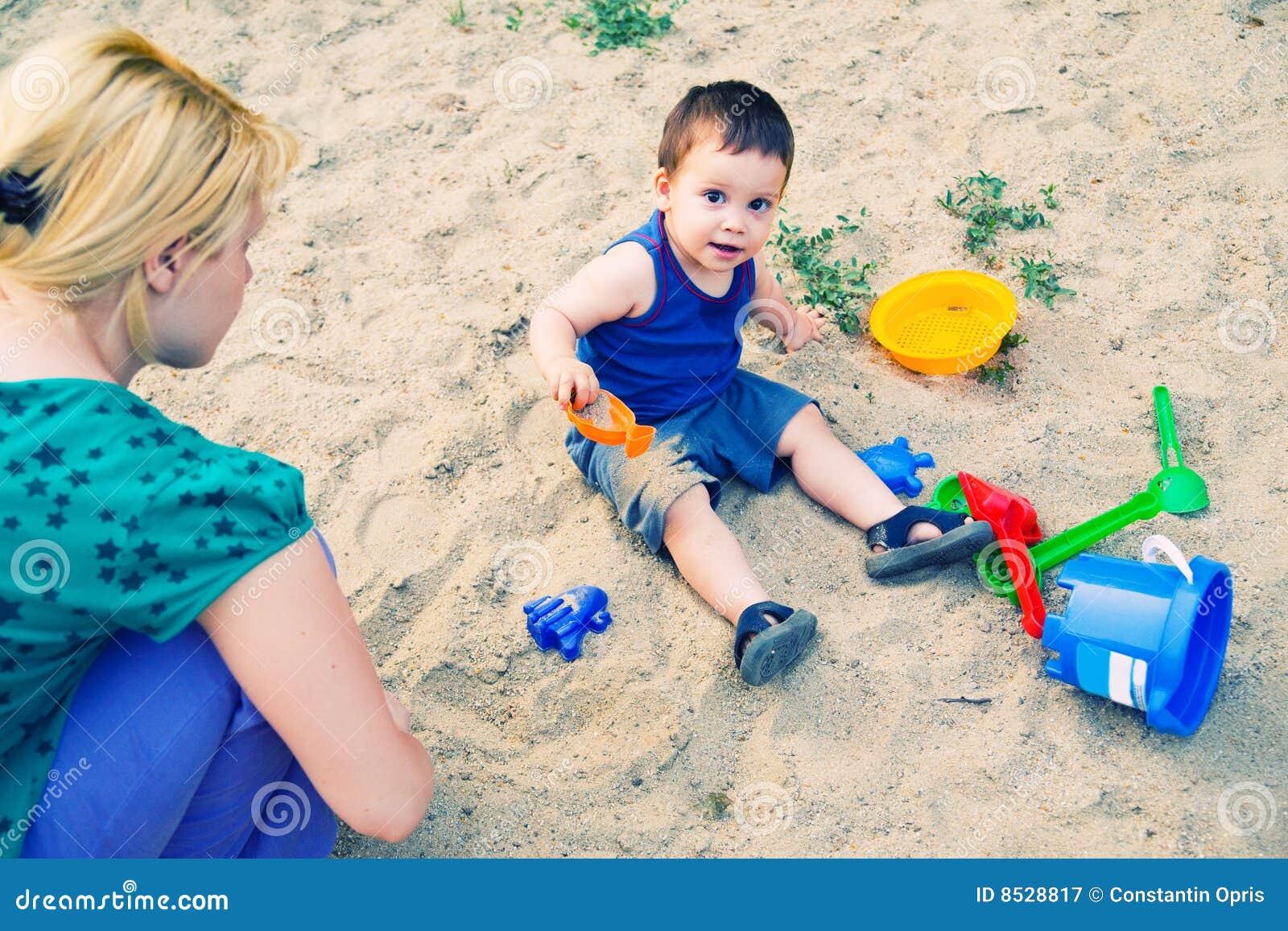 Criança que joga na areia