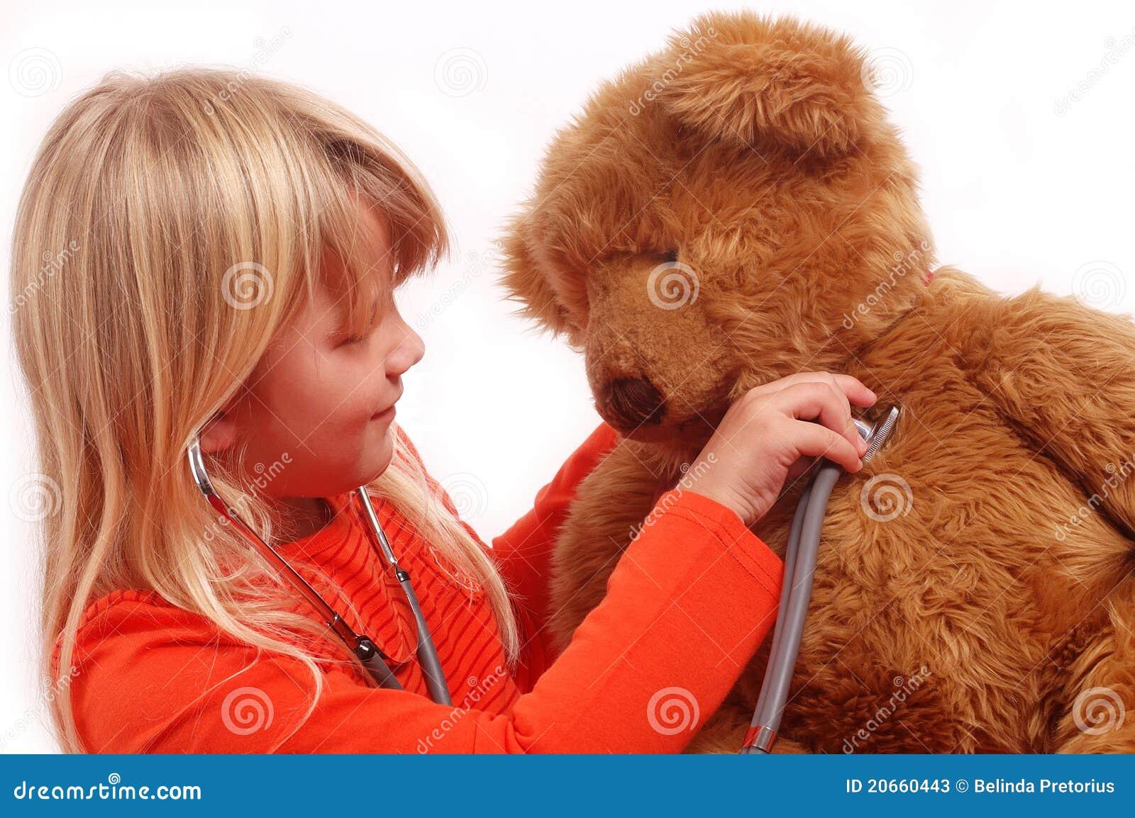 Criança que joga o doutor com seu urso