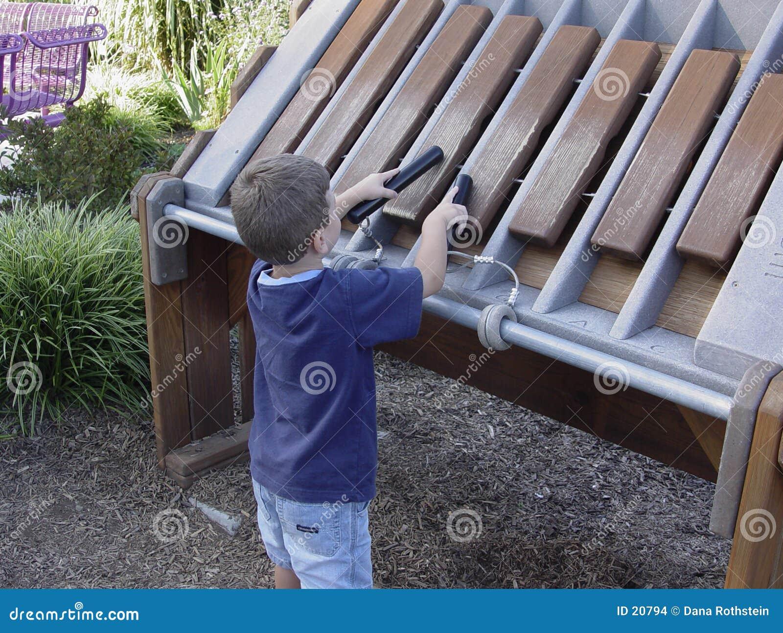 Criança que joga o Xylophone