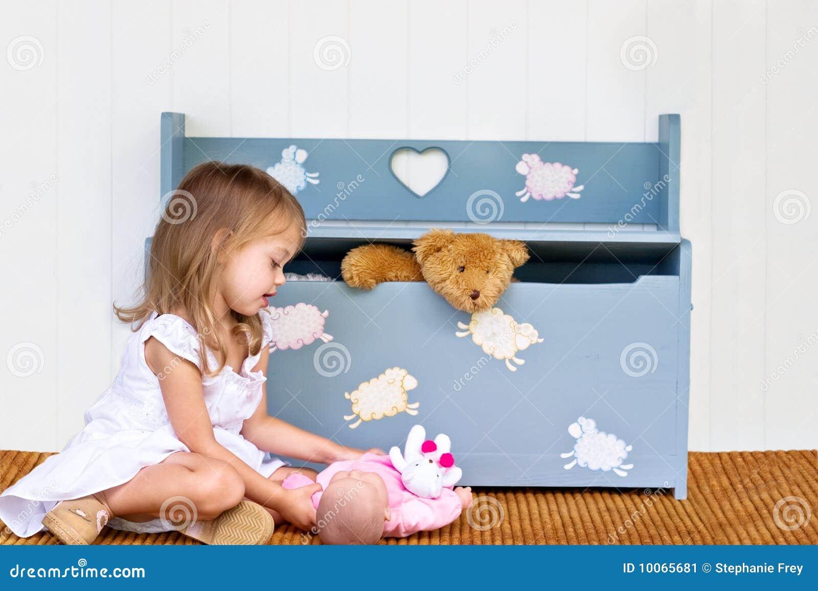 Criança que joga perto da caixa de brinquedo.