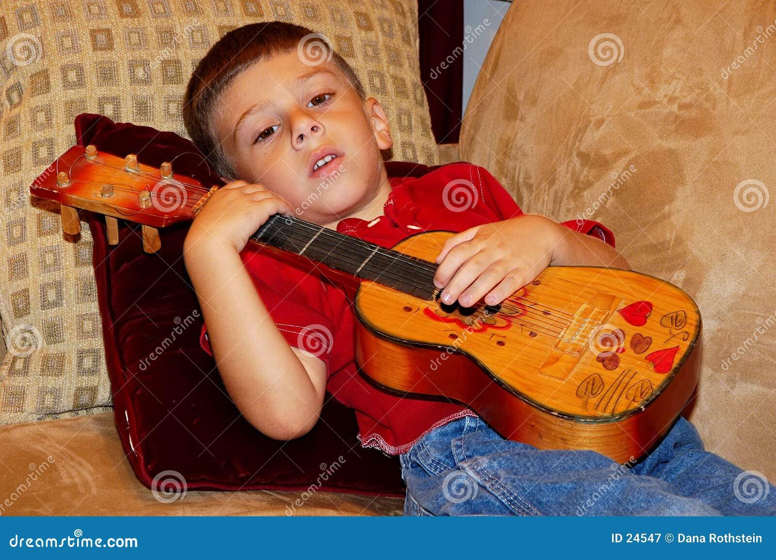 Criança que joga um Ukulele