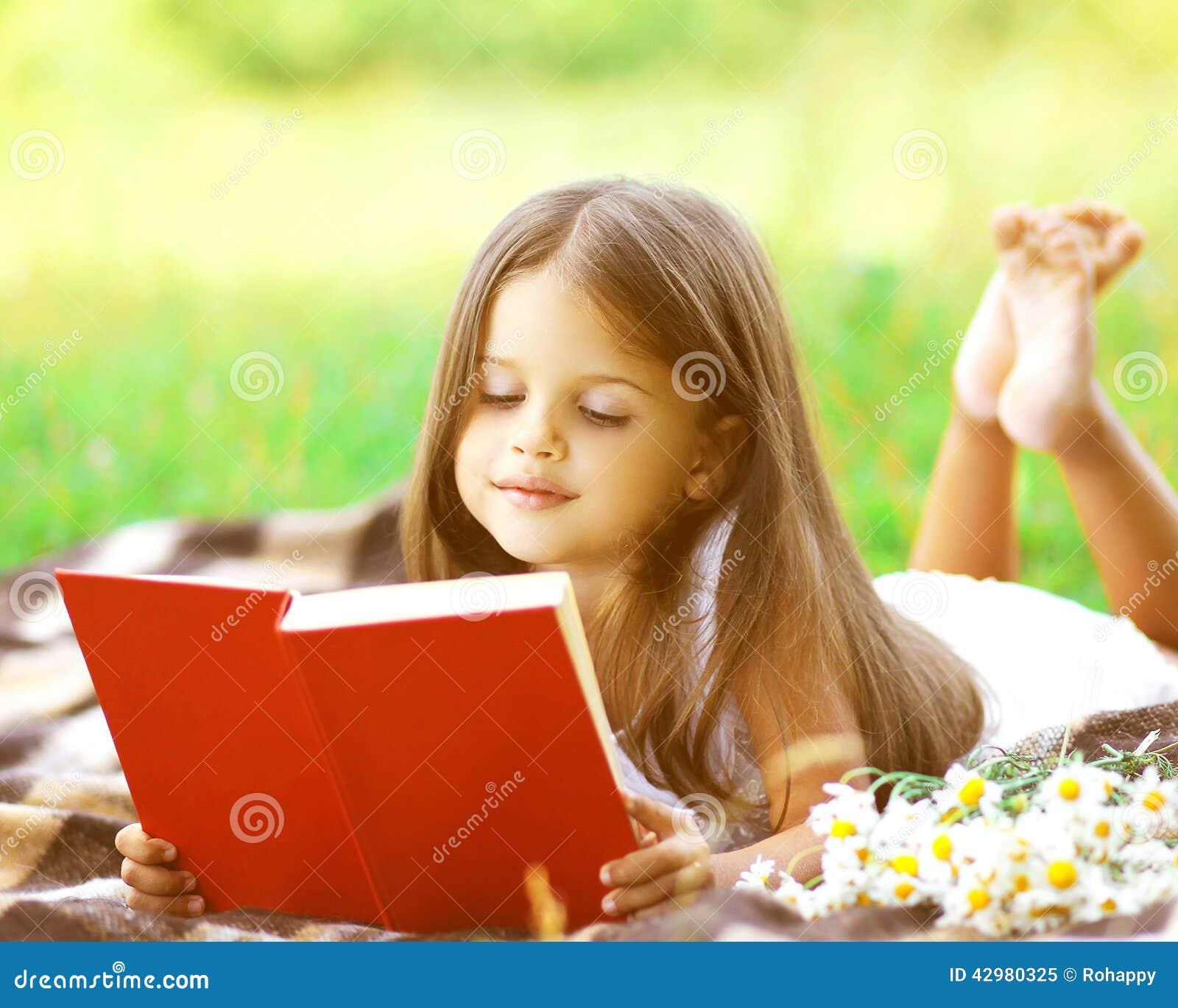 Criança que lê um livro na grama