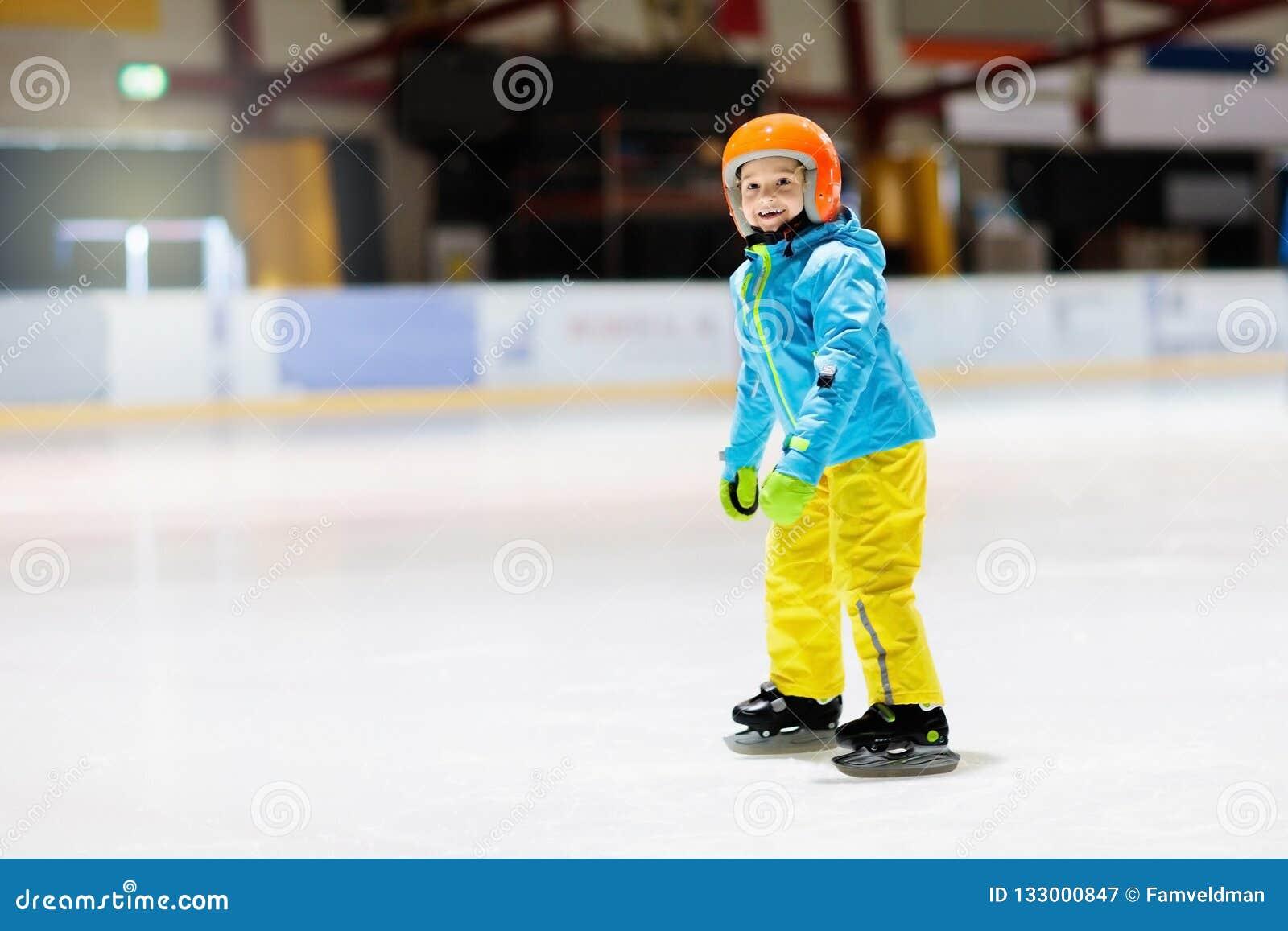 Criança que patina na pista de gelo interna Patim das crianças