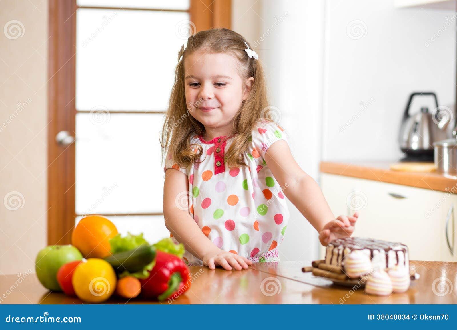 Criança que recusa o alimento prejudicial em favor dos vegetais