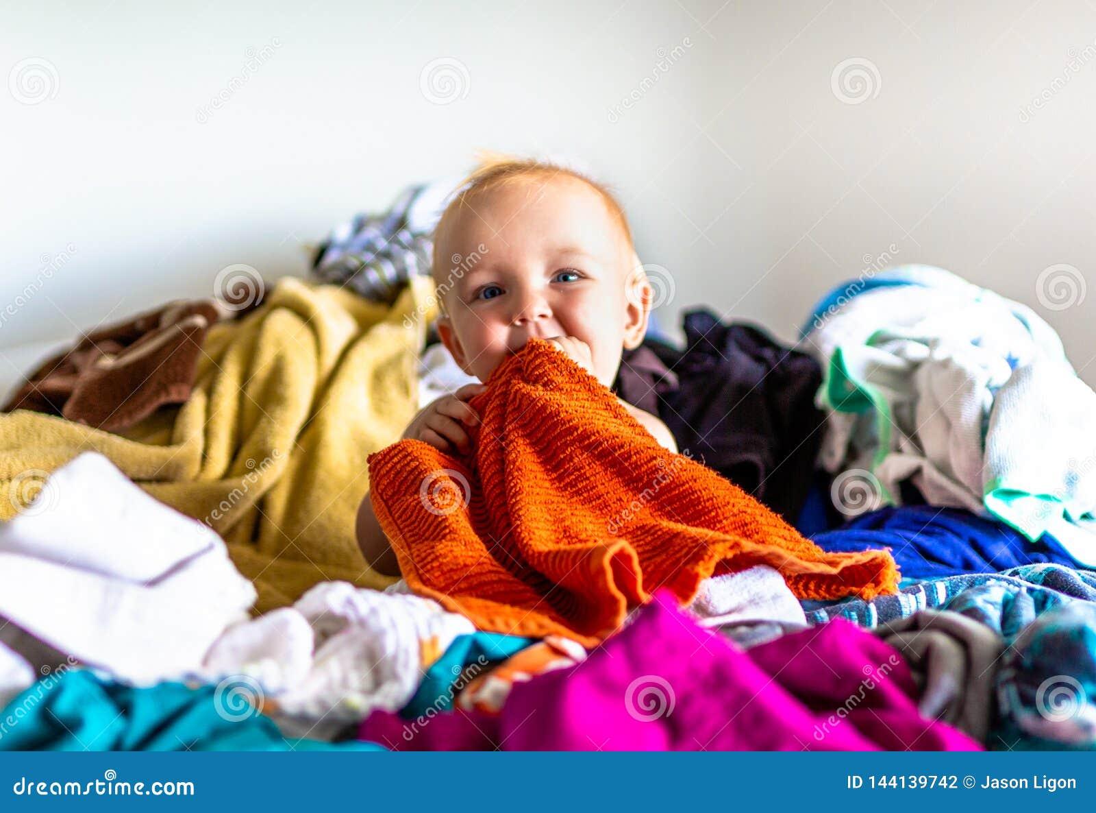 Criança que senta-se na pilha da lavanderia na cama