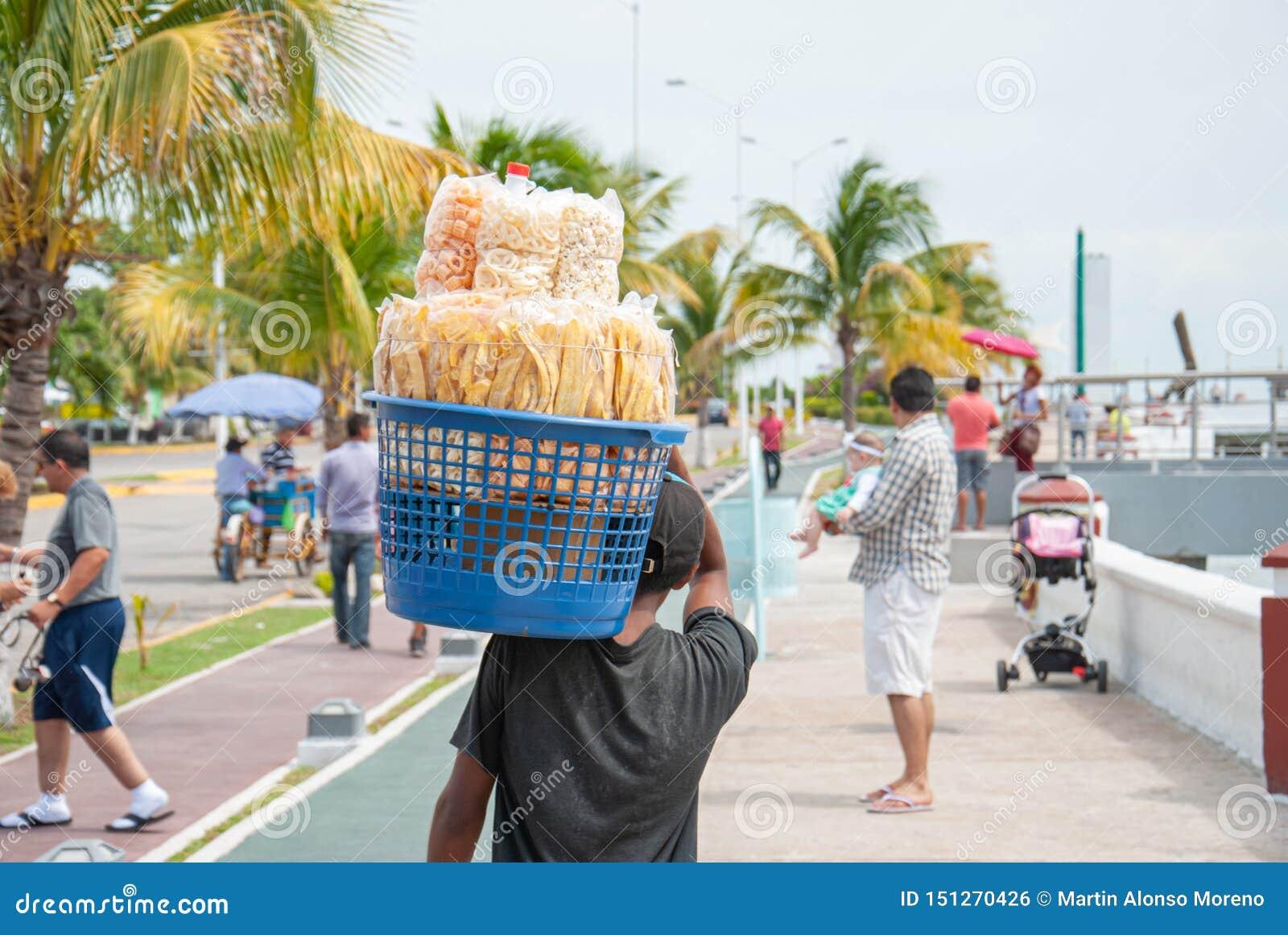 Criança que vende fritos de milho ao longo do passeio marítimo de Campeche México