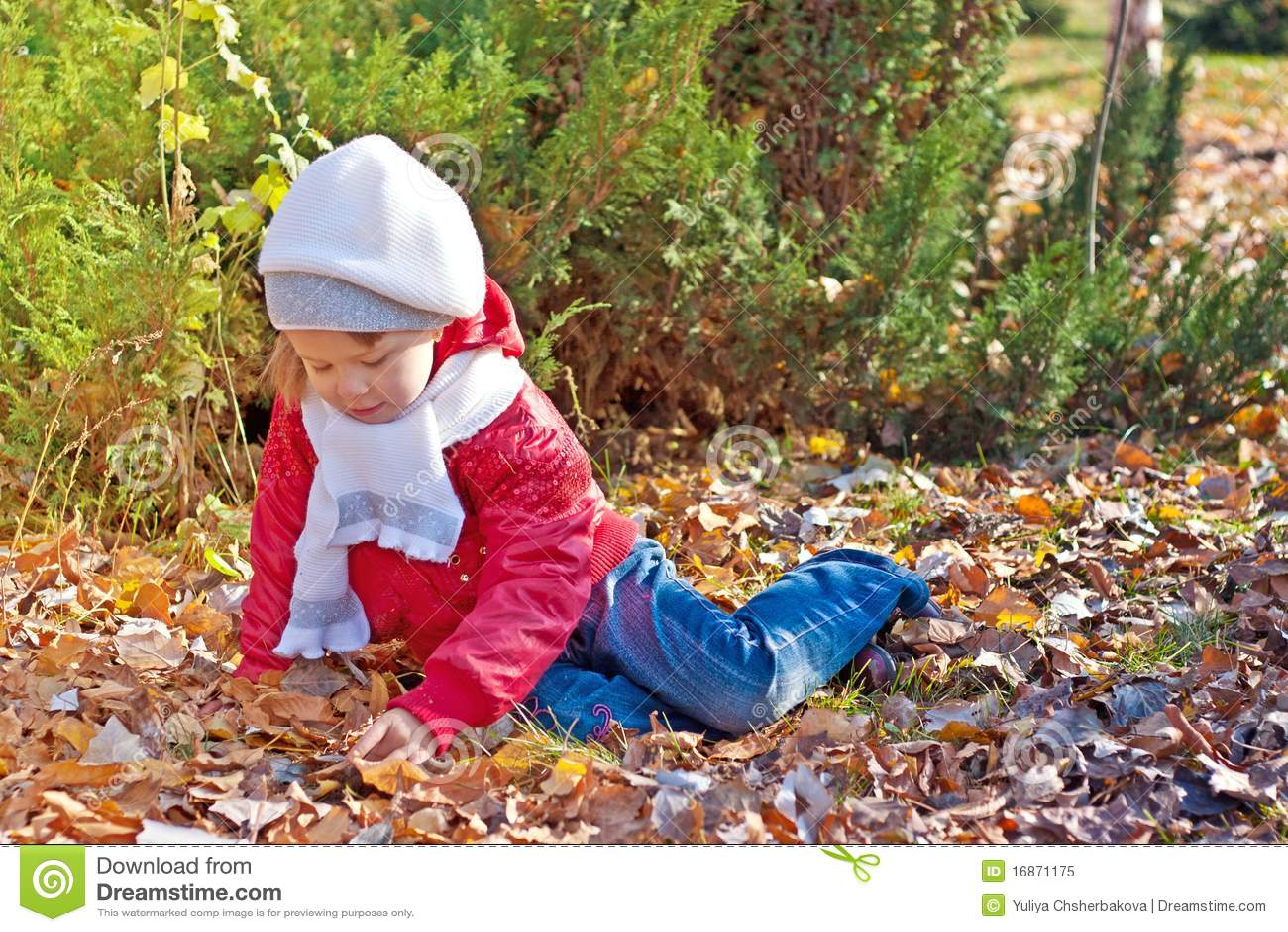 A criança senta-se na terra no parque do outono