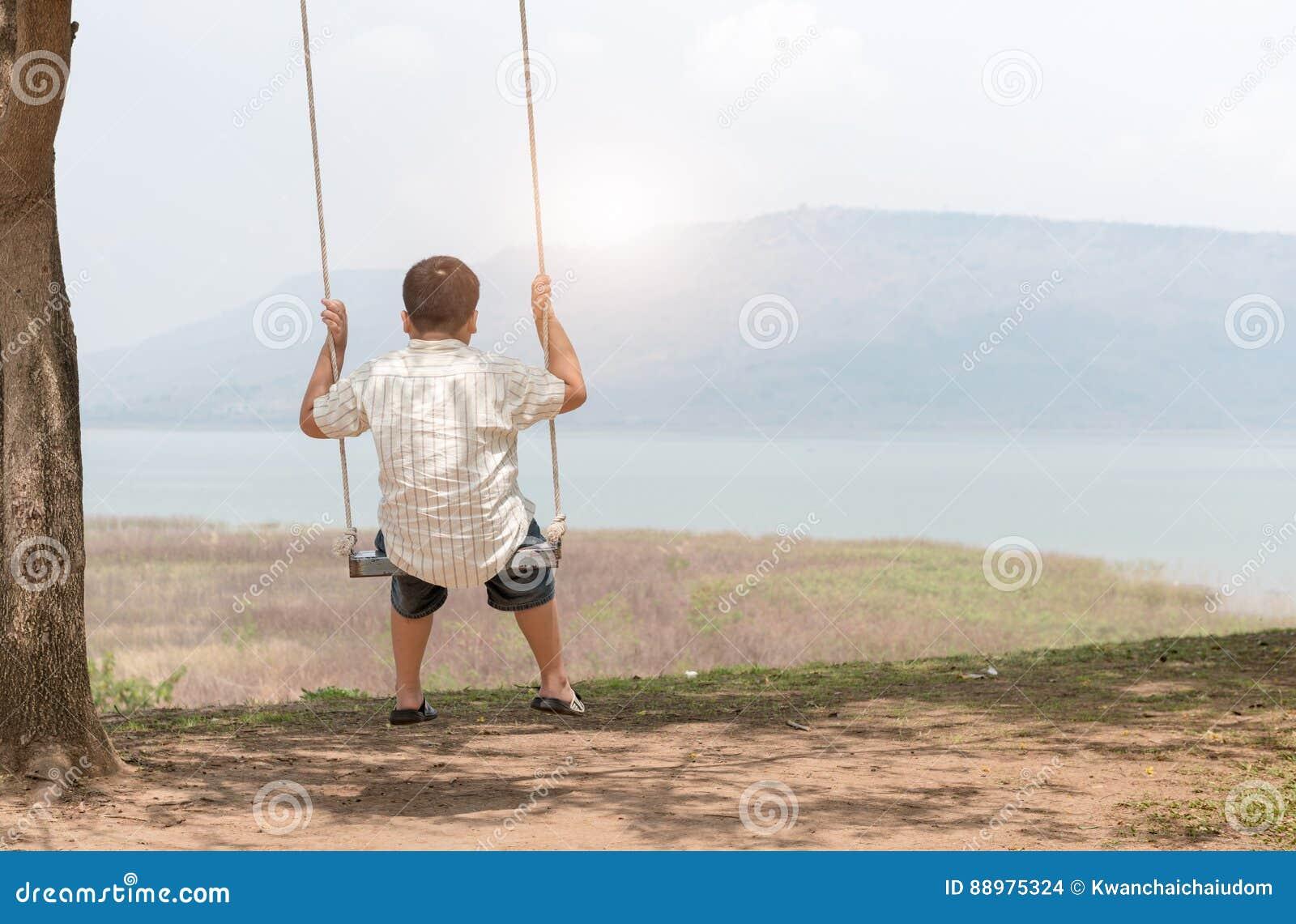 A criança senta-se no assento do balanço, conceito do lazer