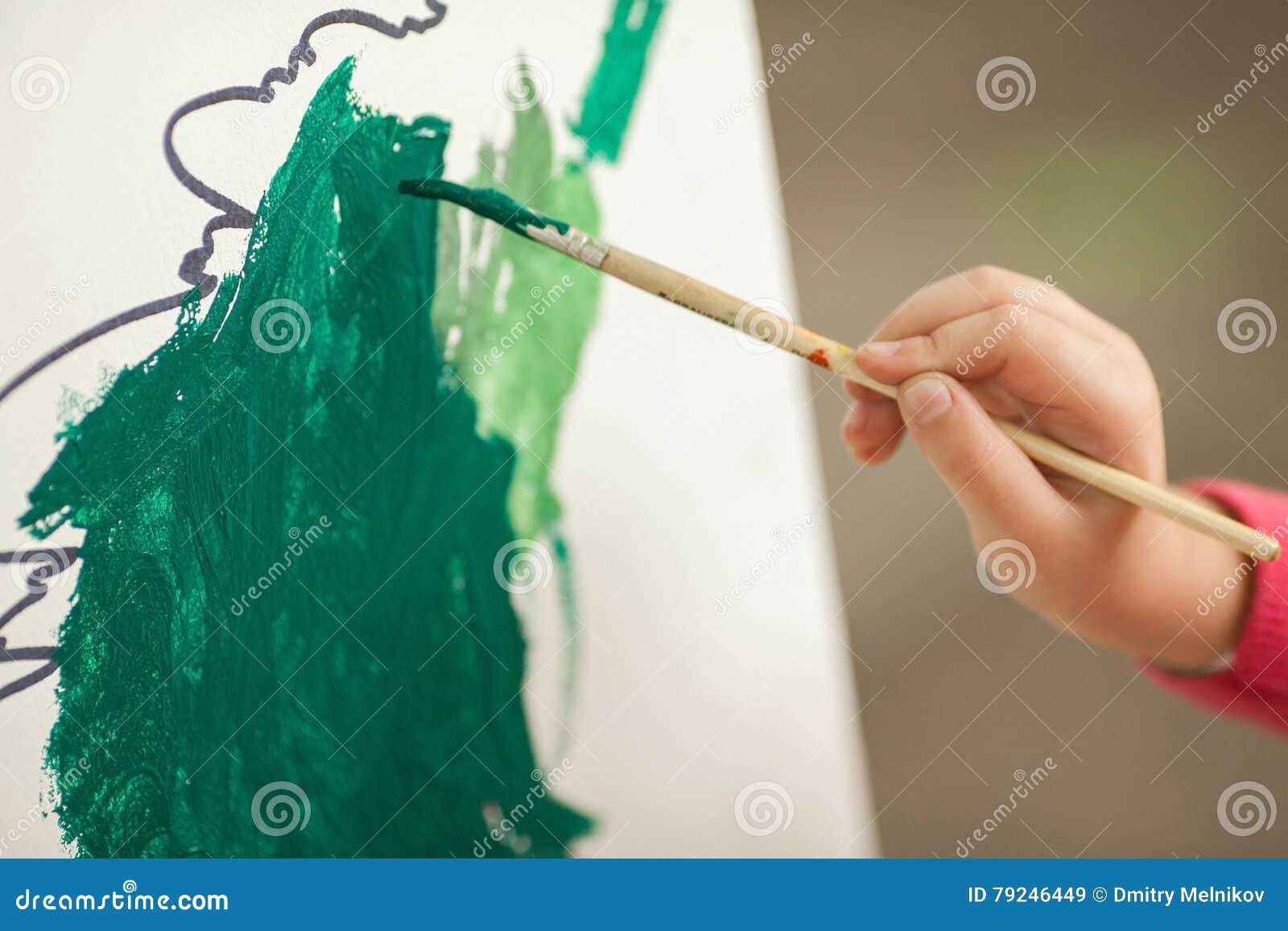 A criança tira pinturas no papel children& x27; desenho de s uma mão de t