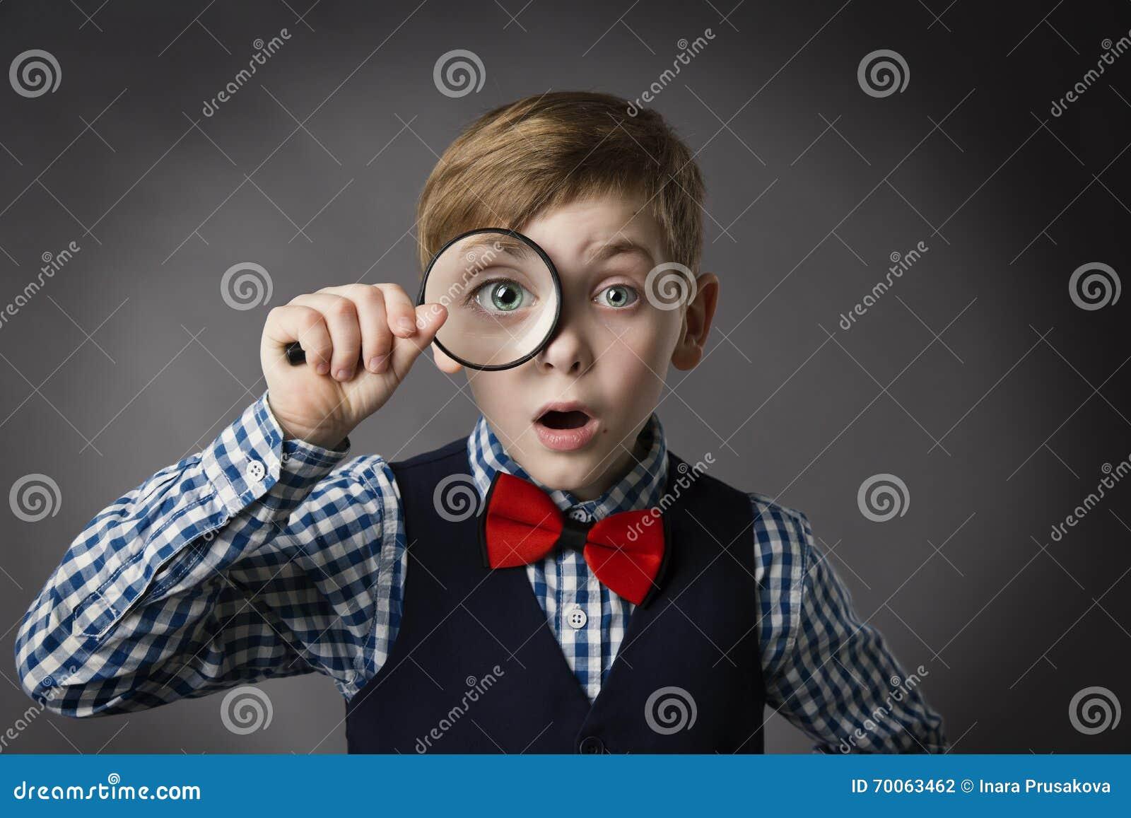A criança vê completamente a lupa, lente da lente de aumento do olho da criança
