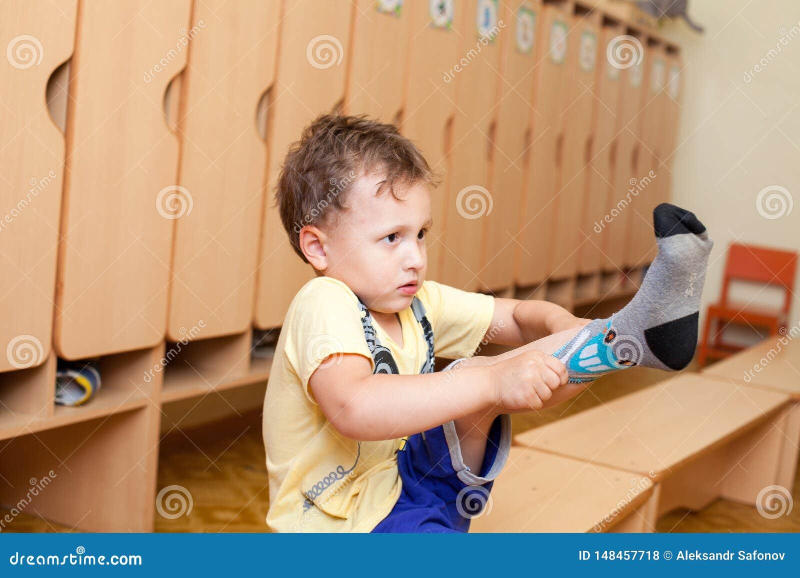A criança veste peúgas no jardim de infância