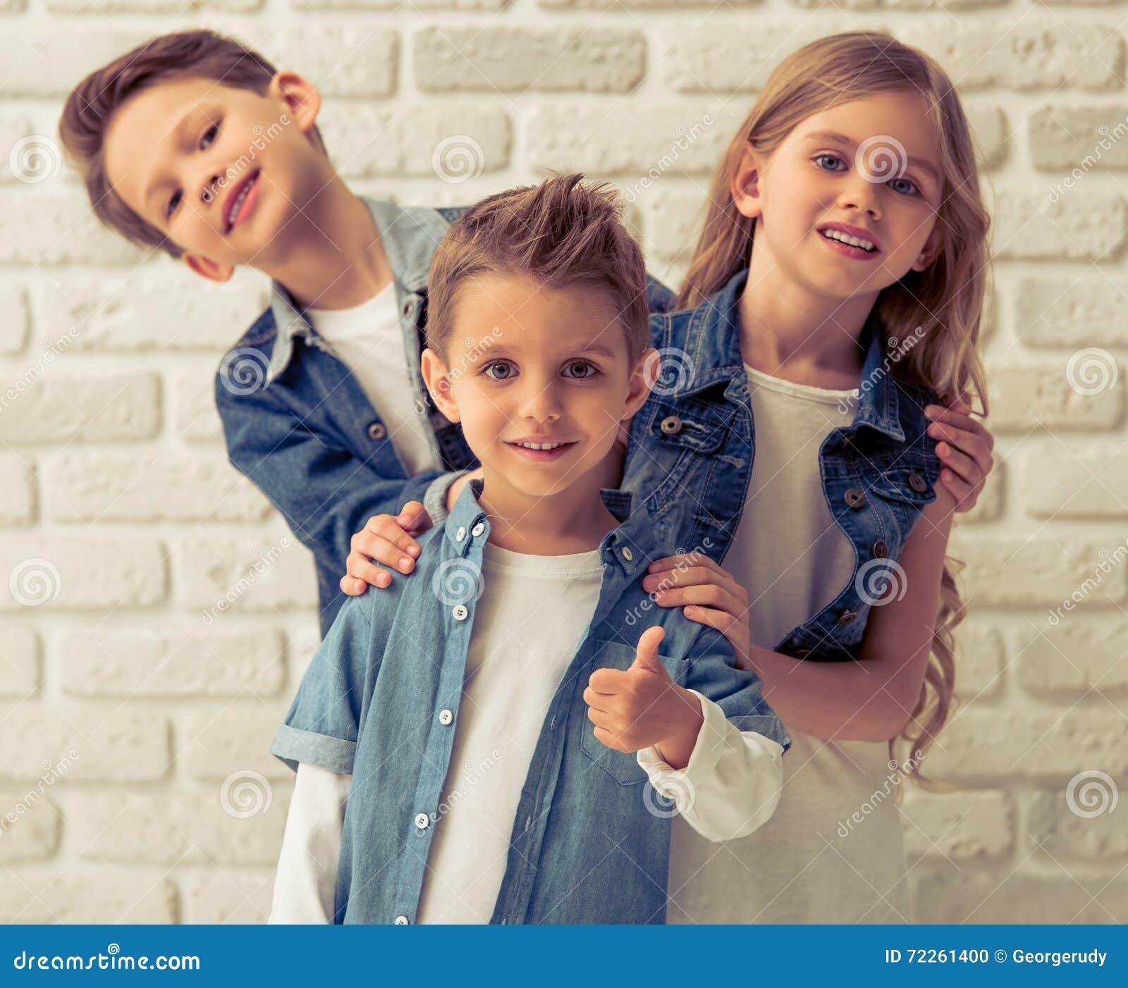 32be93717 As crianças bonitos na roupa à moda estão olhando a câmera e o sorriso,  estando um por um contra a parede de tijolo branca O menino dianteiro está  mostrando ...