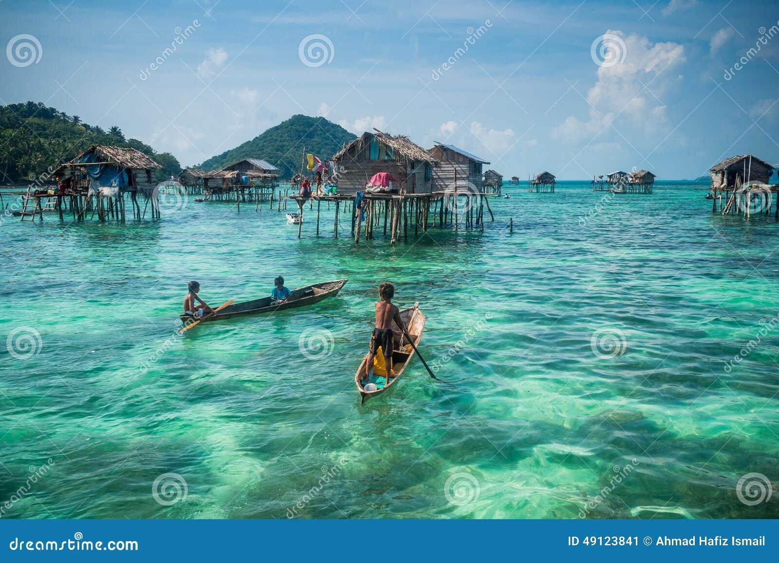 Crianças aciganadas do mar em sua sampana com sua casa em pernas de pau no