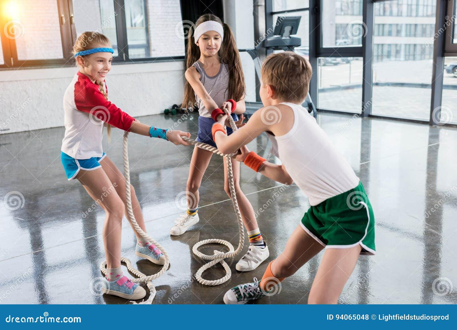 Crianças adoráveis no treinamento do sportswear com cordas no estúdio da aptidão