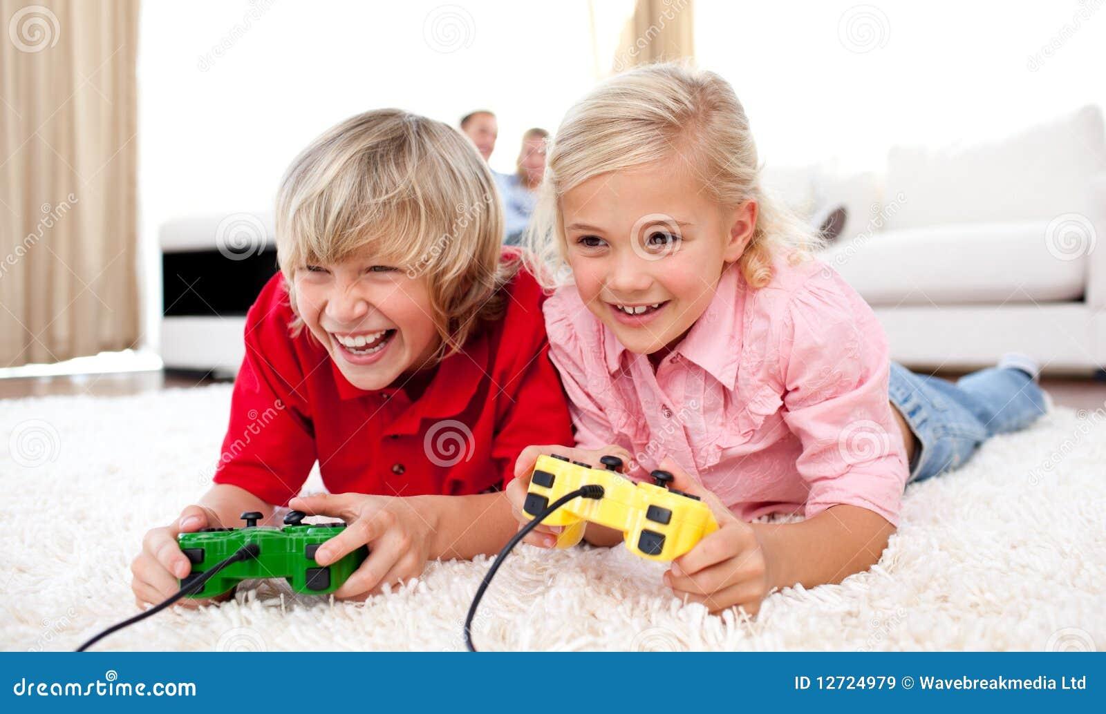 Crianças adoráveis que jogam os jogos video