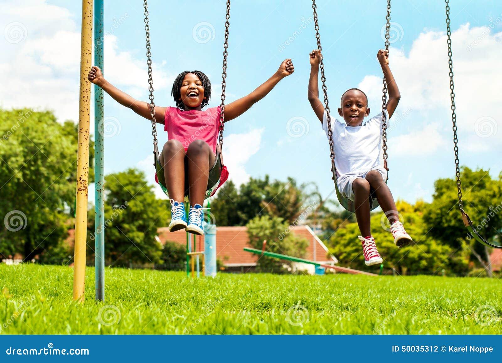 Crianças africanas que jogam no balanço na vizinhança