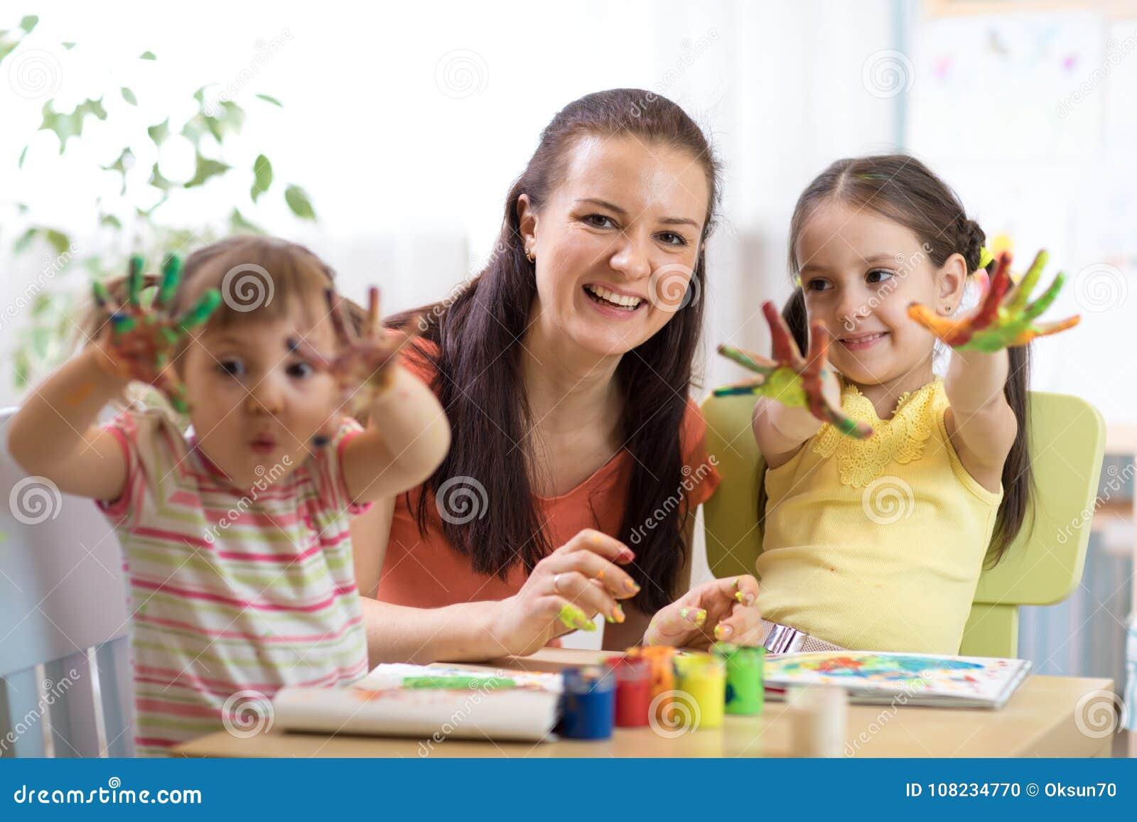 Crianças alegres e sua mãe que têm o divertimento e que mostram as mãos pintadas em pinturas coloridas