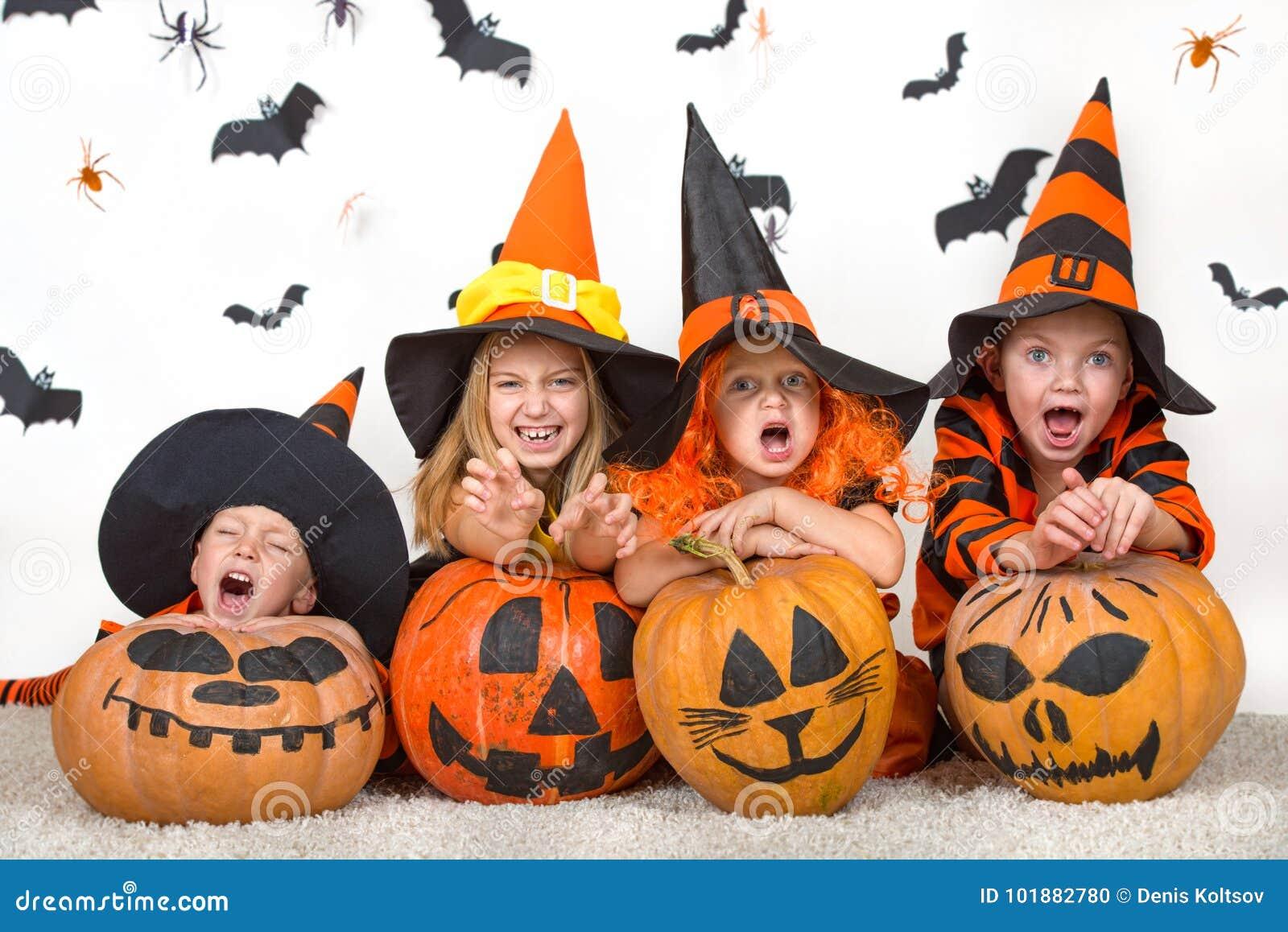 Crianças alegres em trajes do Dia das Bruxas que comemoram o Dia das Bruxas
