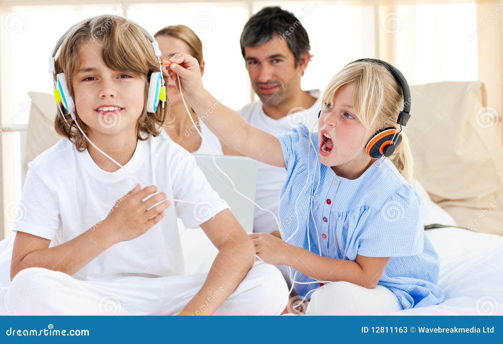 Crianças alegres que têm o divertimento e a música de escuta