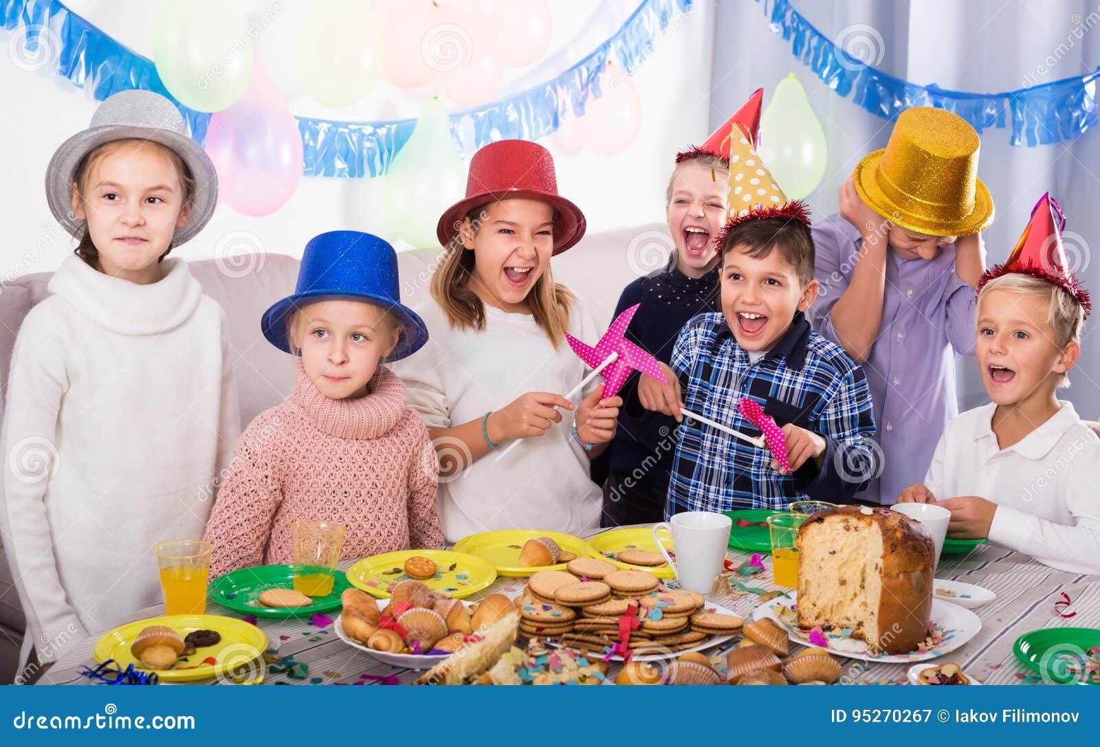 Crianças amigáveis do grupo que têm o aniversário dos friend's do partido