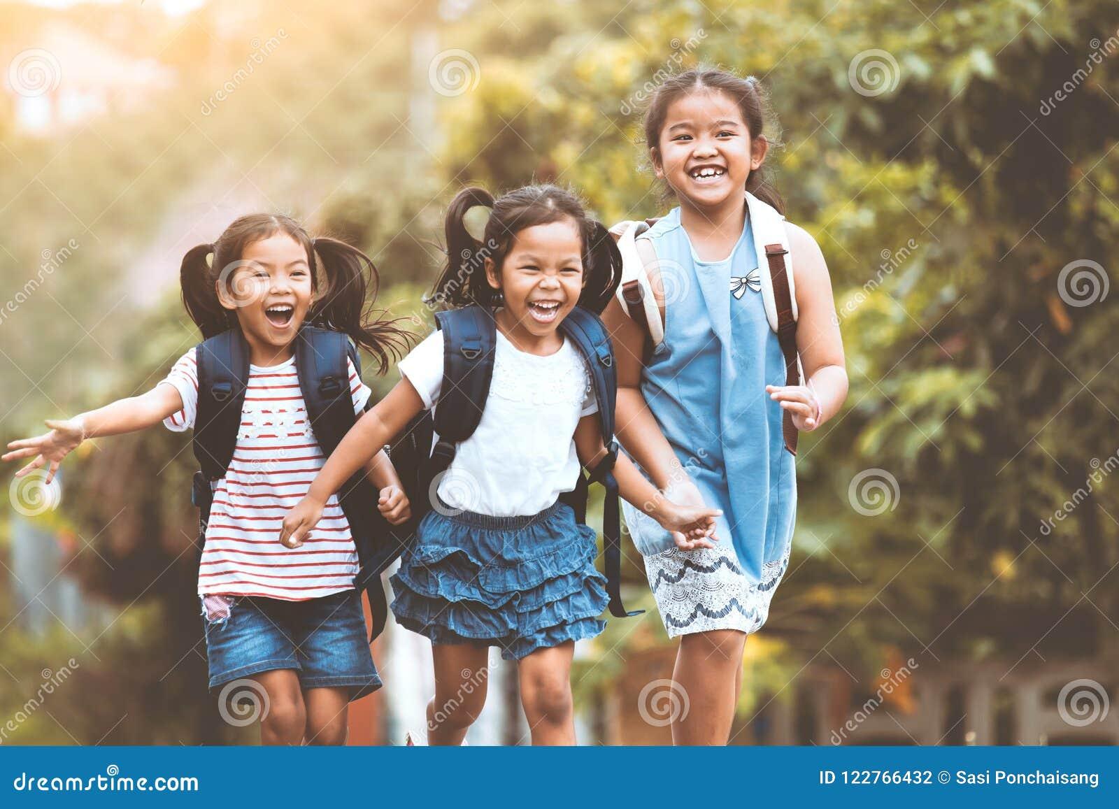 Crianças asiáticas do aluno com corredor da trouxa