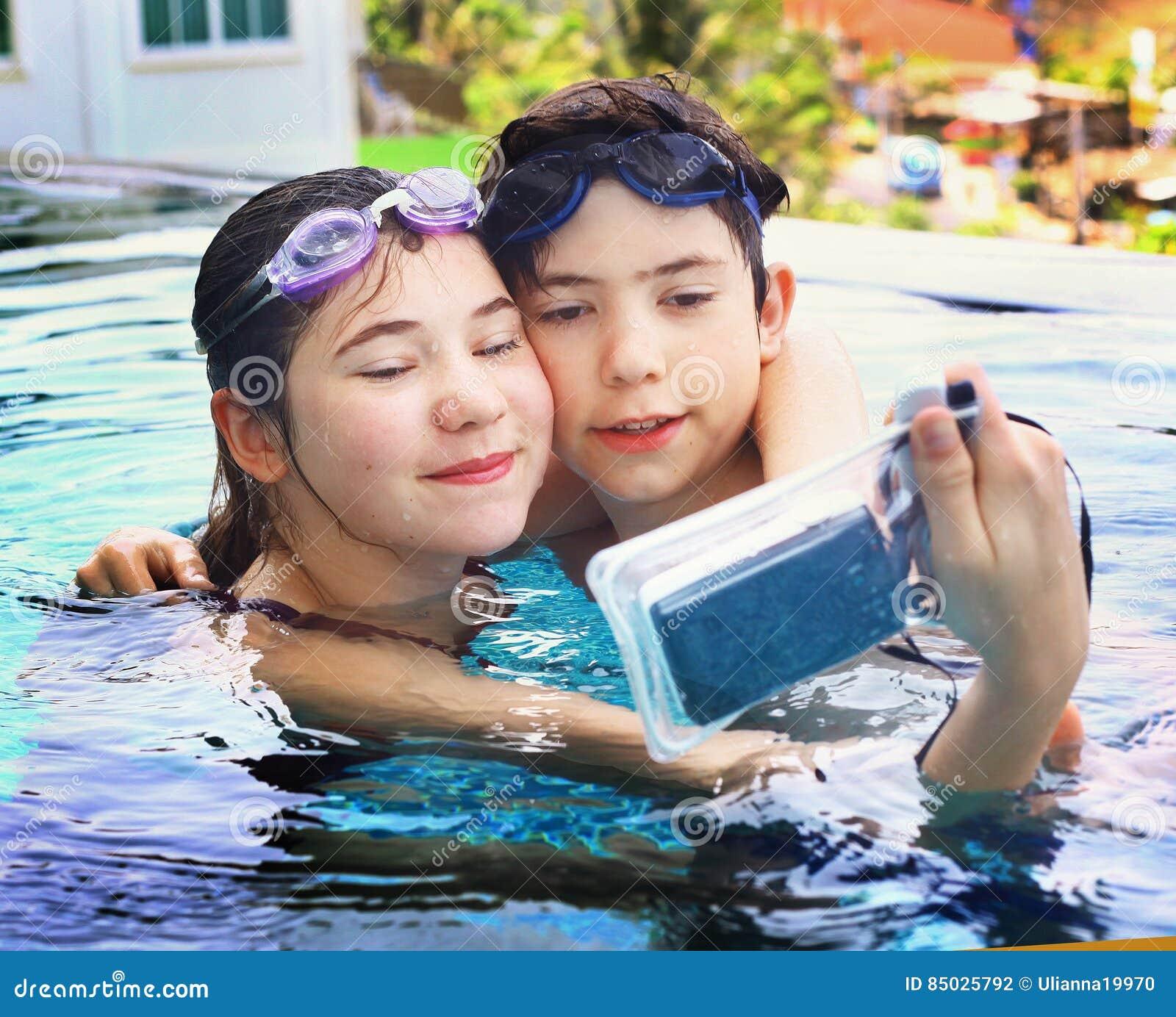Crianças com a câmera subaquática na piscina