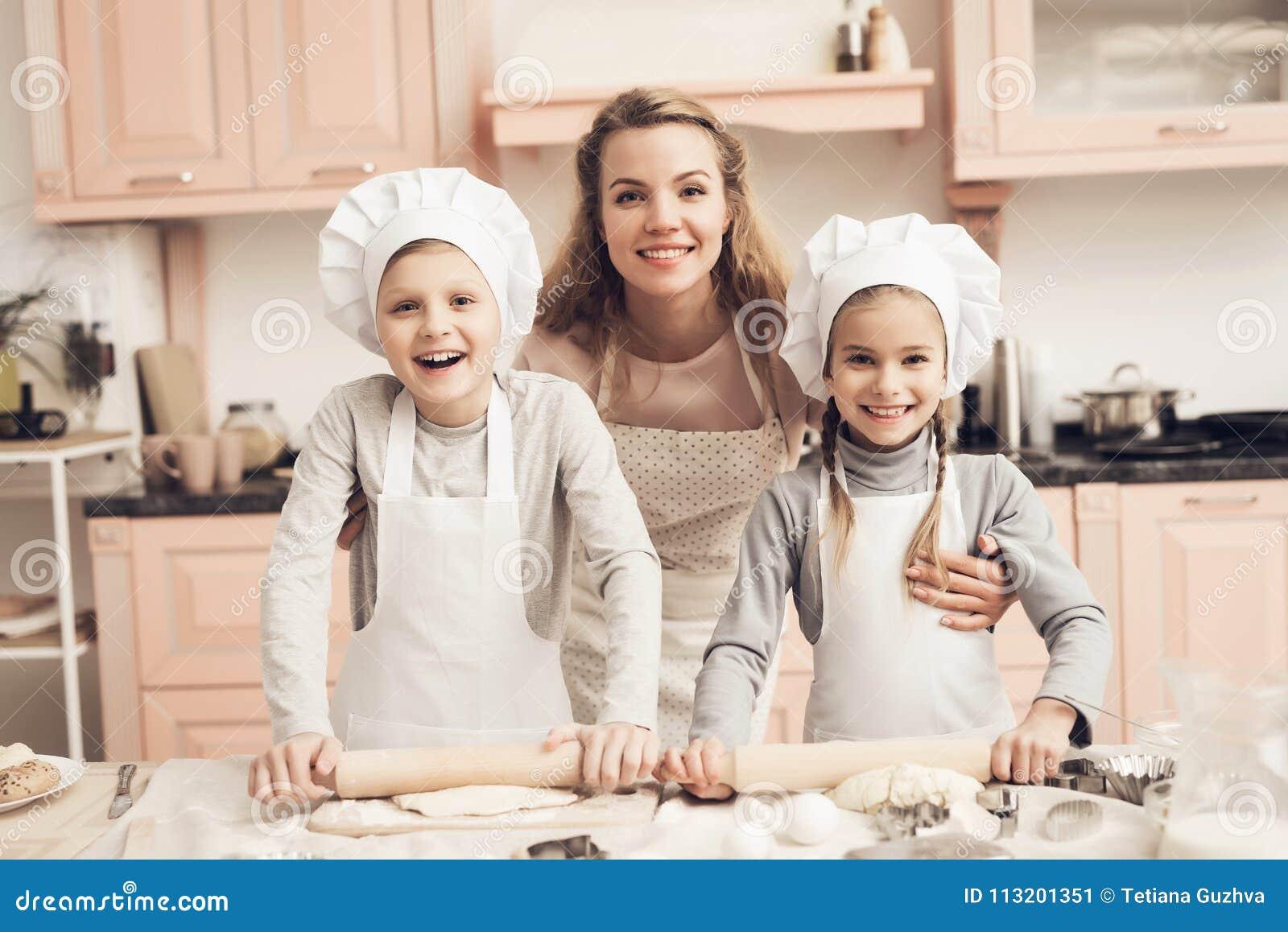 Crianças com a mãe na cozinha A família está pronta para desenrolar a massa