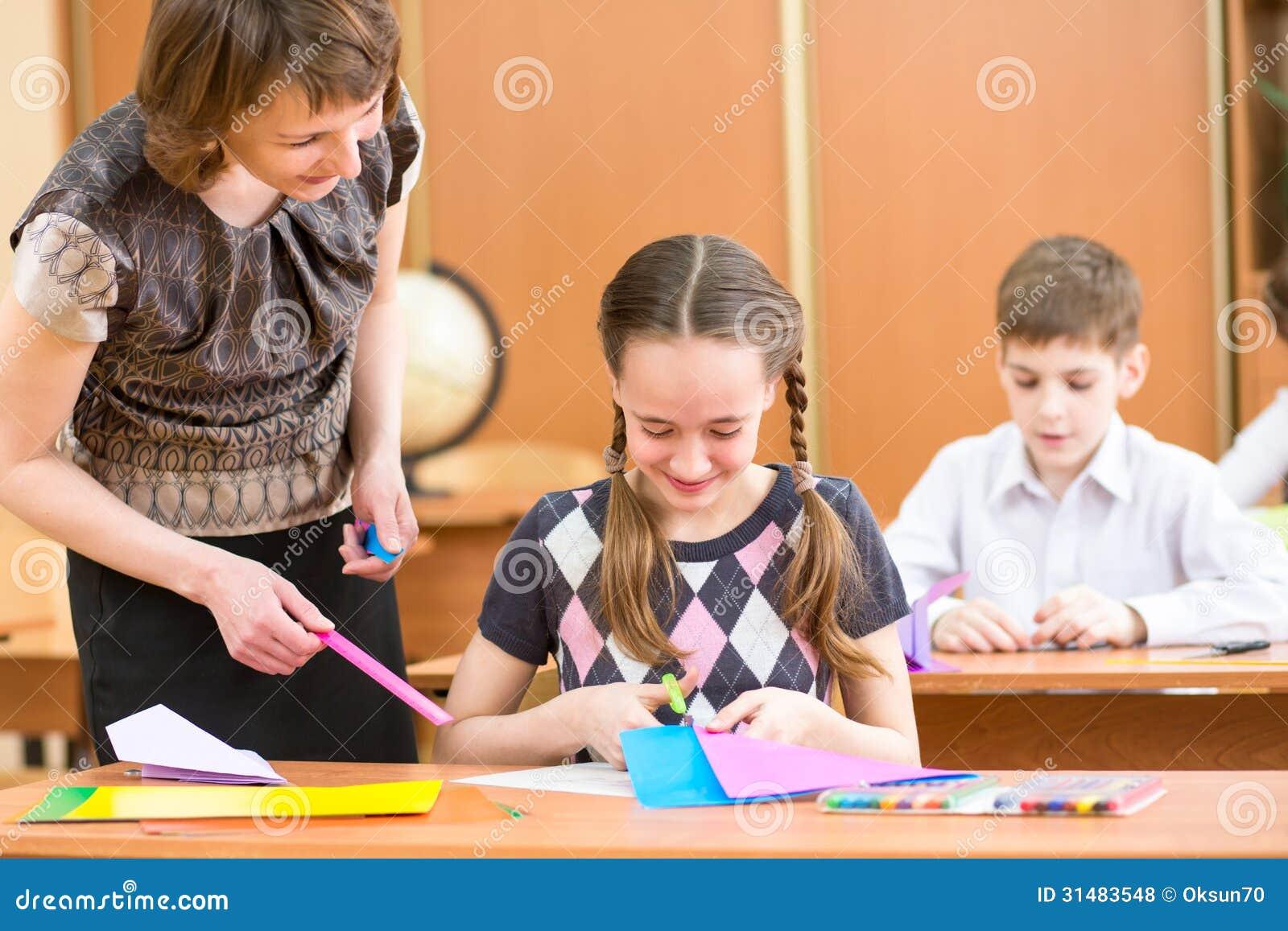 Crianças da escola e trabalho do professor na lição.