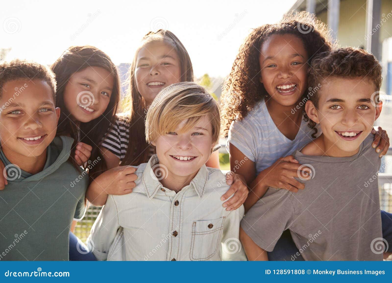 Crianças da escola primária que sorriem à câmera durante a ruptura da escola