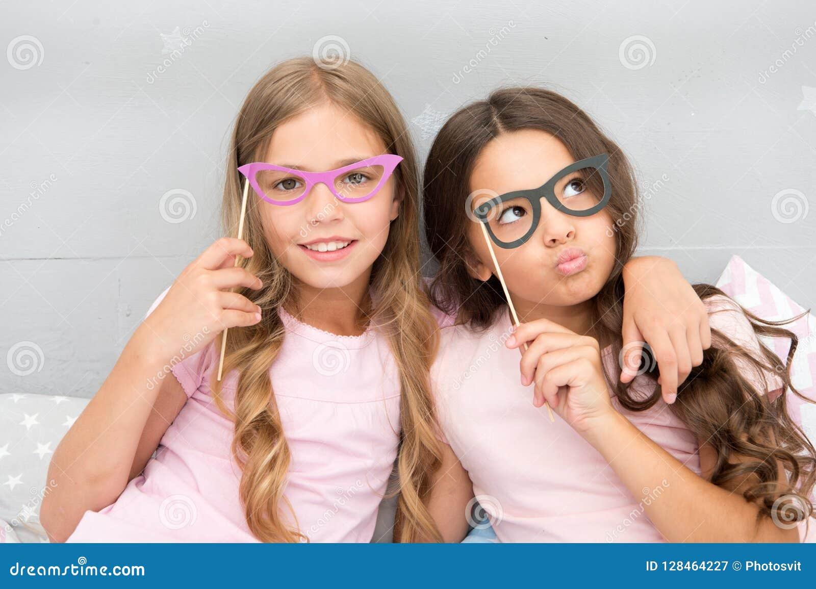 Crianças das meninas que levantam com os suportes da cabine da foto das careta Conceito do partido de pijamas Amigos de meninas q